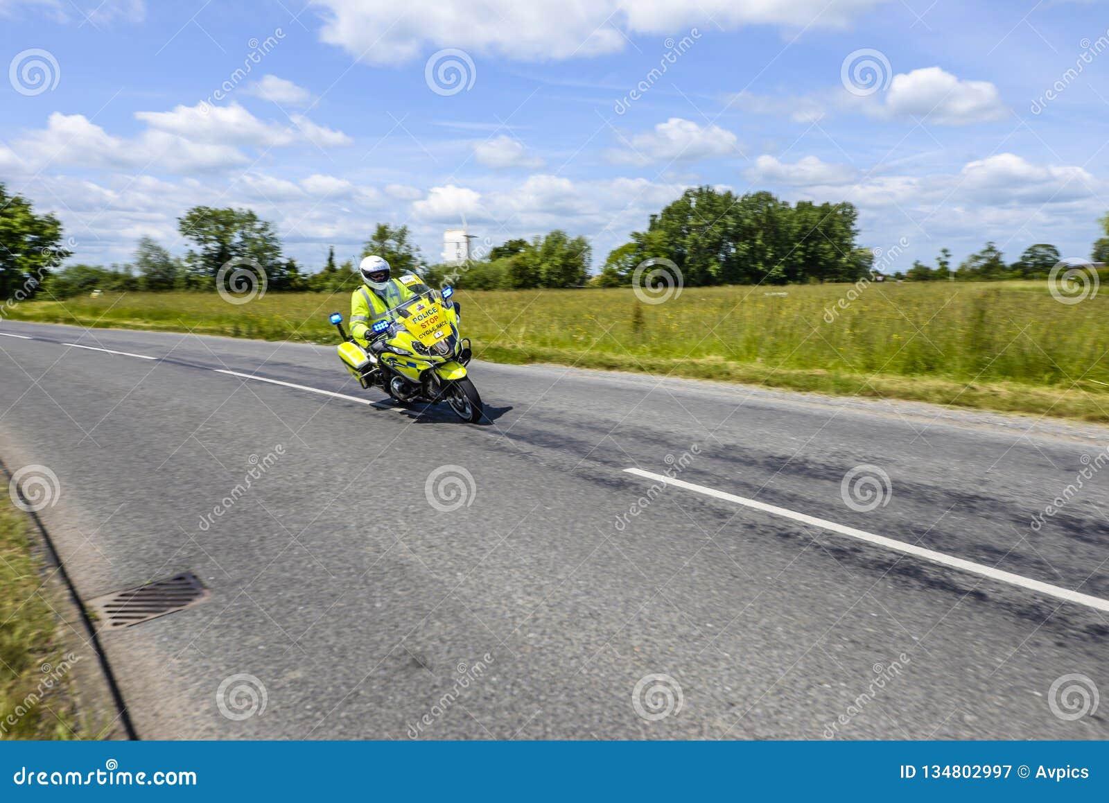 Milicyjna motocyklu outrider jazda przy prędkością przez Brytyjskiej wsi