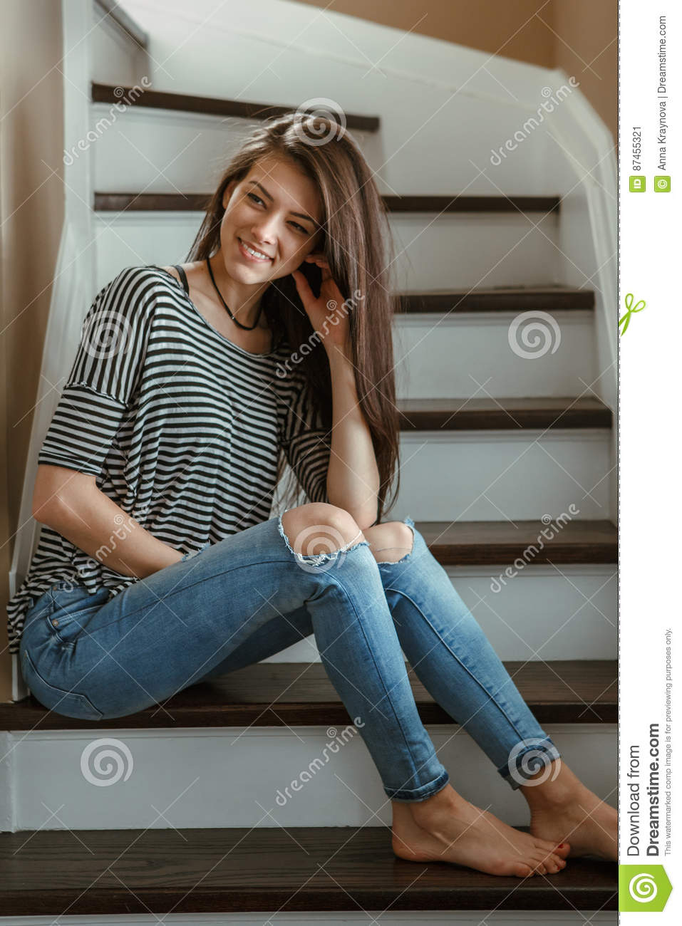 f2c39a4643e Closeup portrait of smiling Caucasian young beautiful woman model with messy  long hair in ripped blue jeans and striped t-shirt sitting on stairs indoor  ...