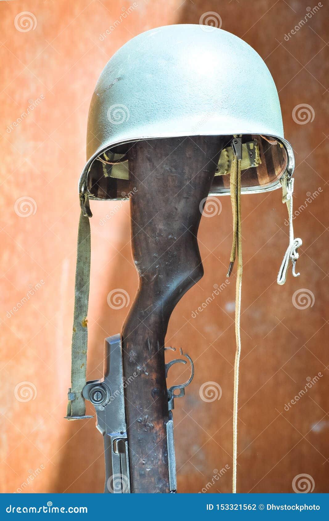Militär hjälm som stöttas på ett skjutvapen Begrepp av den okända soldaten