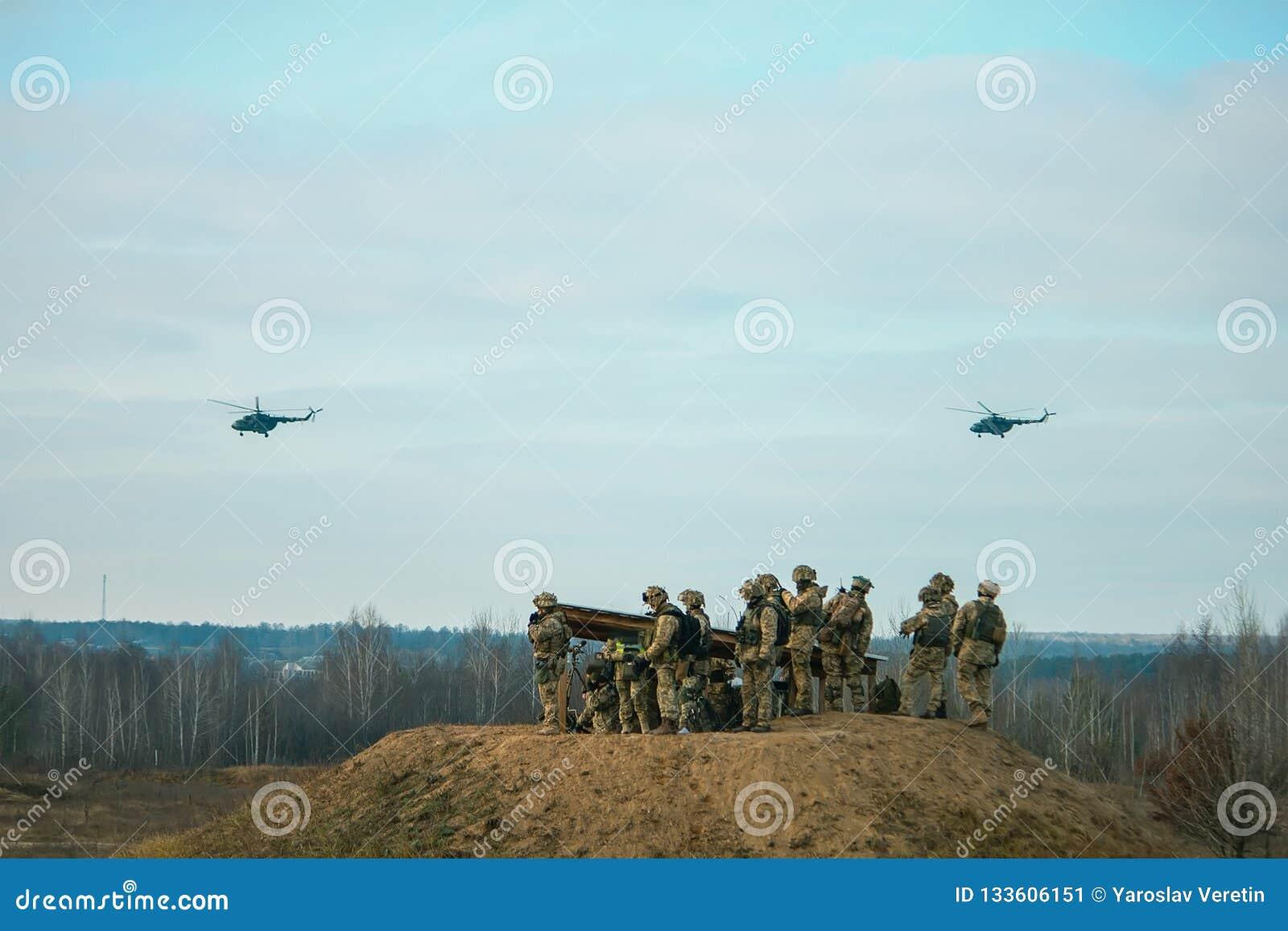Militära arméhelikoptrar som flyger ovanför militärt fält