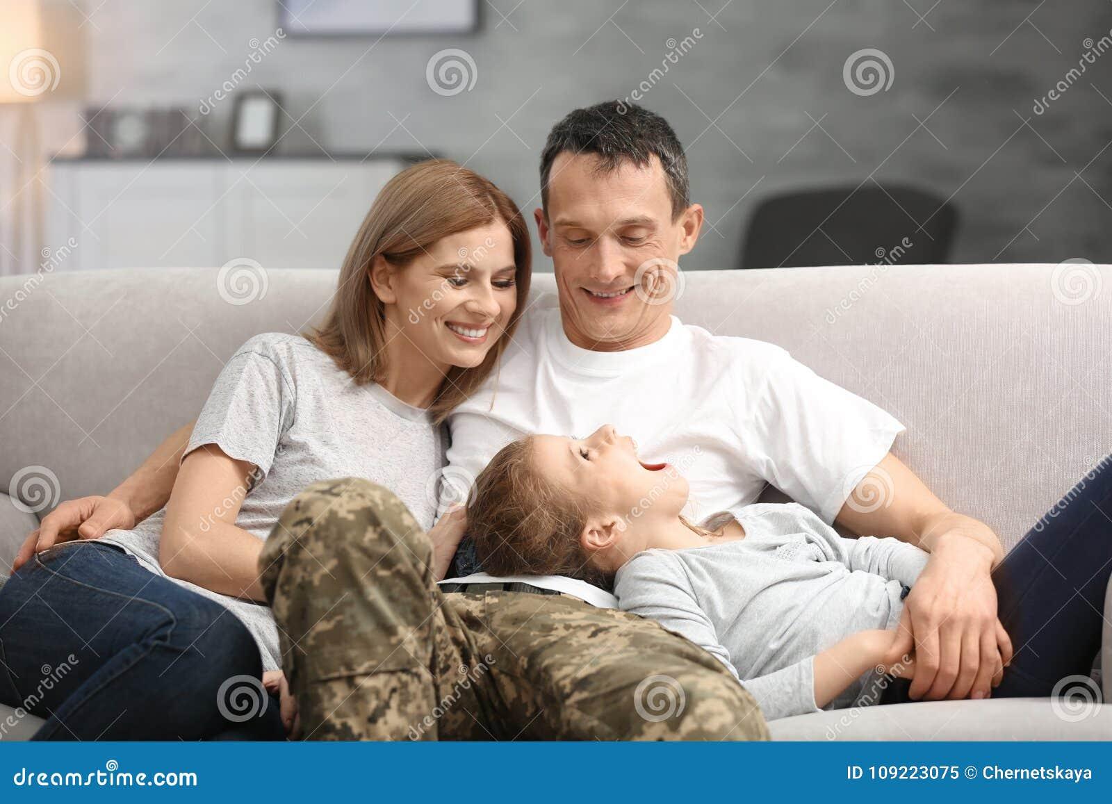 Militärvater mit seiner Familie auf Sofa