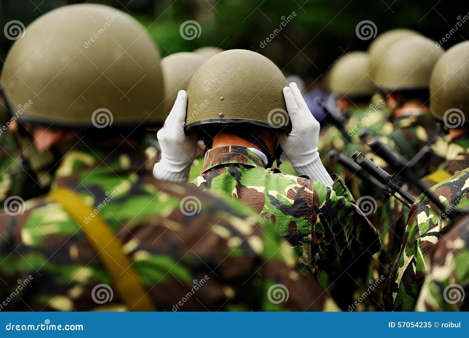 Militair in eenvormige camouflage schikkend zijn helm