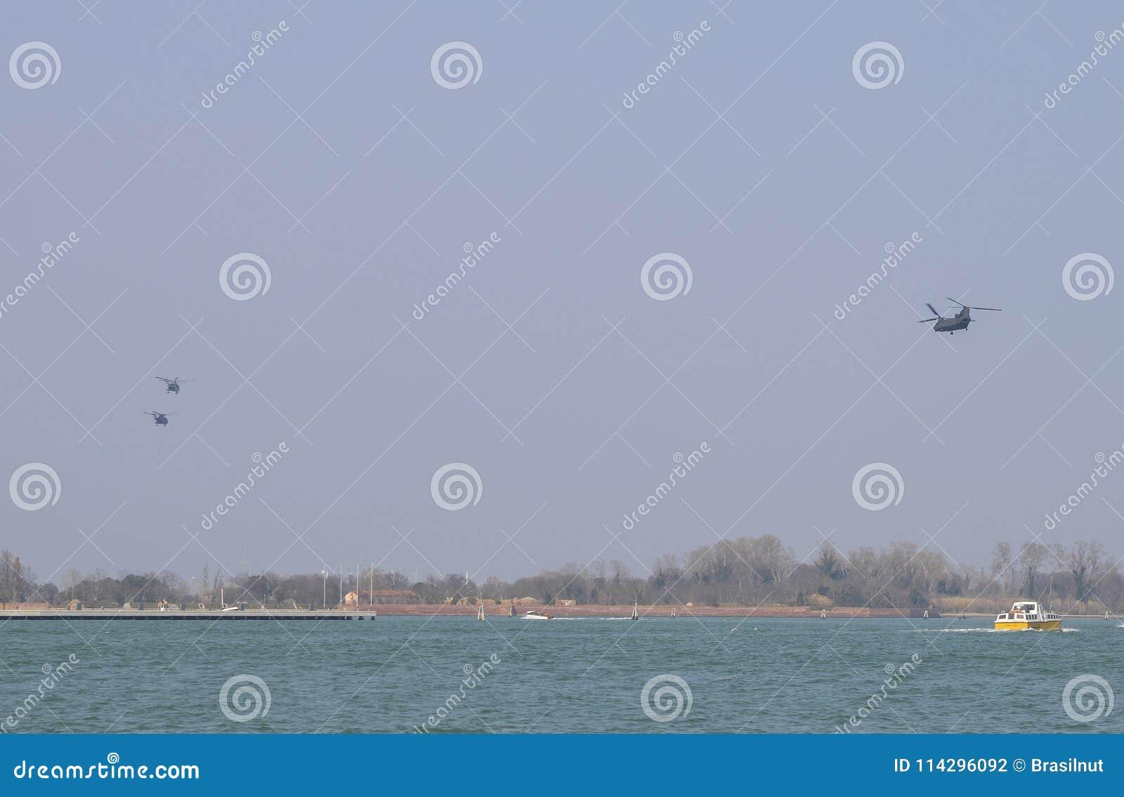 Militaire Helikopters in vorming over de Venetiaanse lagunerubriek naar Aviano-Luchtmachtbasis in Noordoostelijk Italië