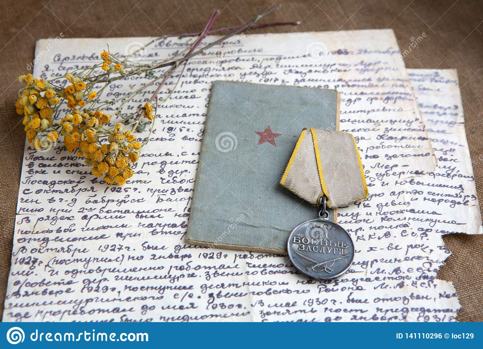 Military merit medal, old letter on canvas. Relics, close-up. Dry flowers of tansy
