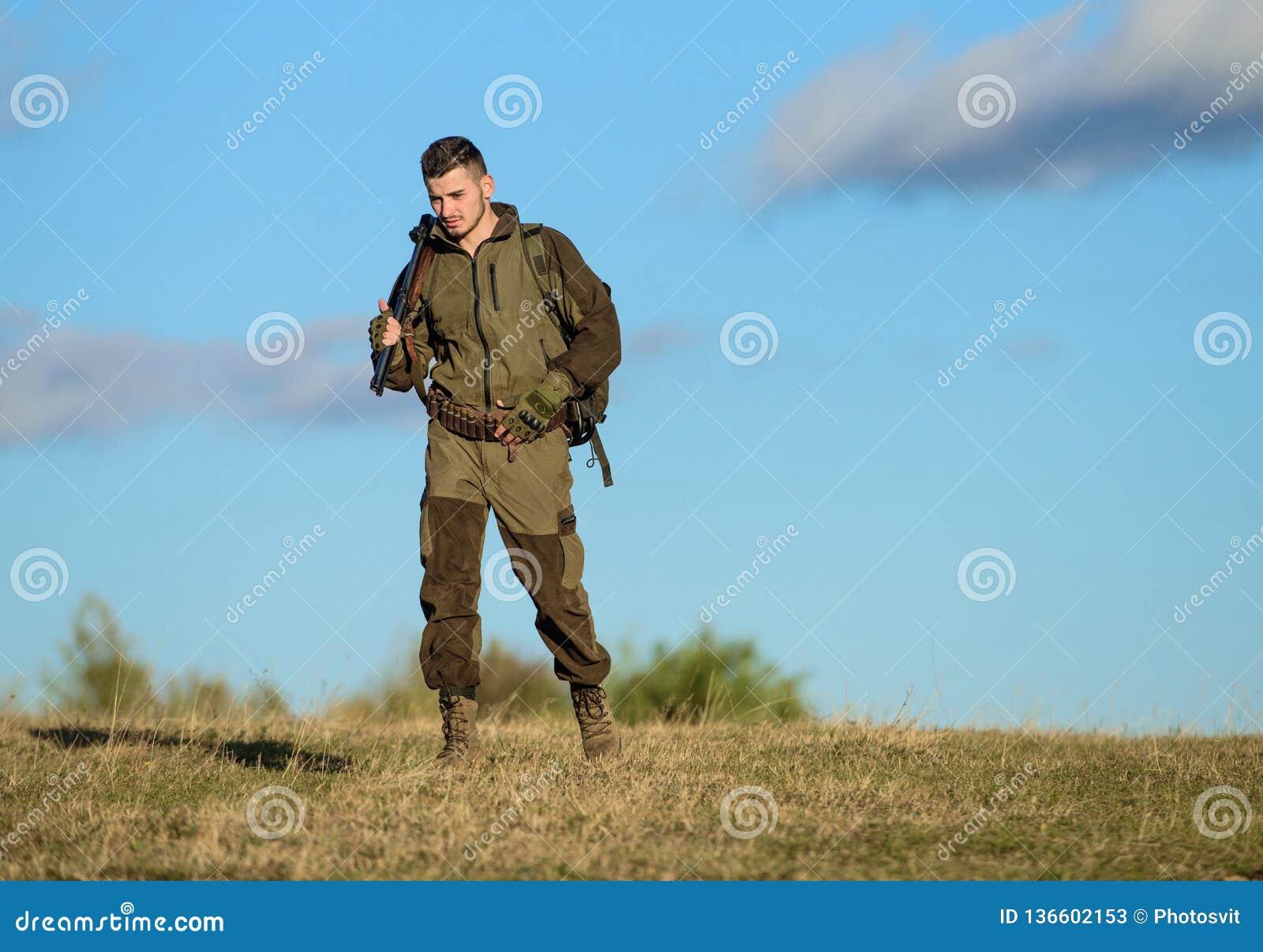 Miljö för grabbjaktnatur Manlig hobbyaktivitet Jaktvapenvapen eller gevär Manjägaren bär blå himmel för geväret