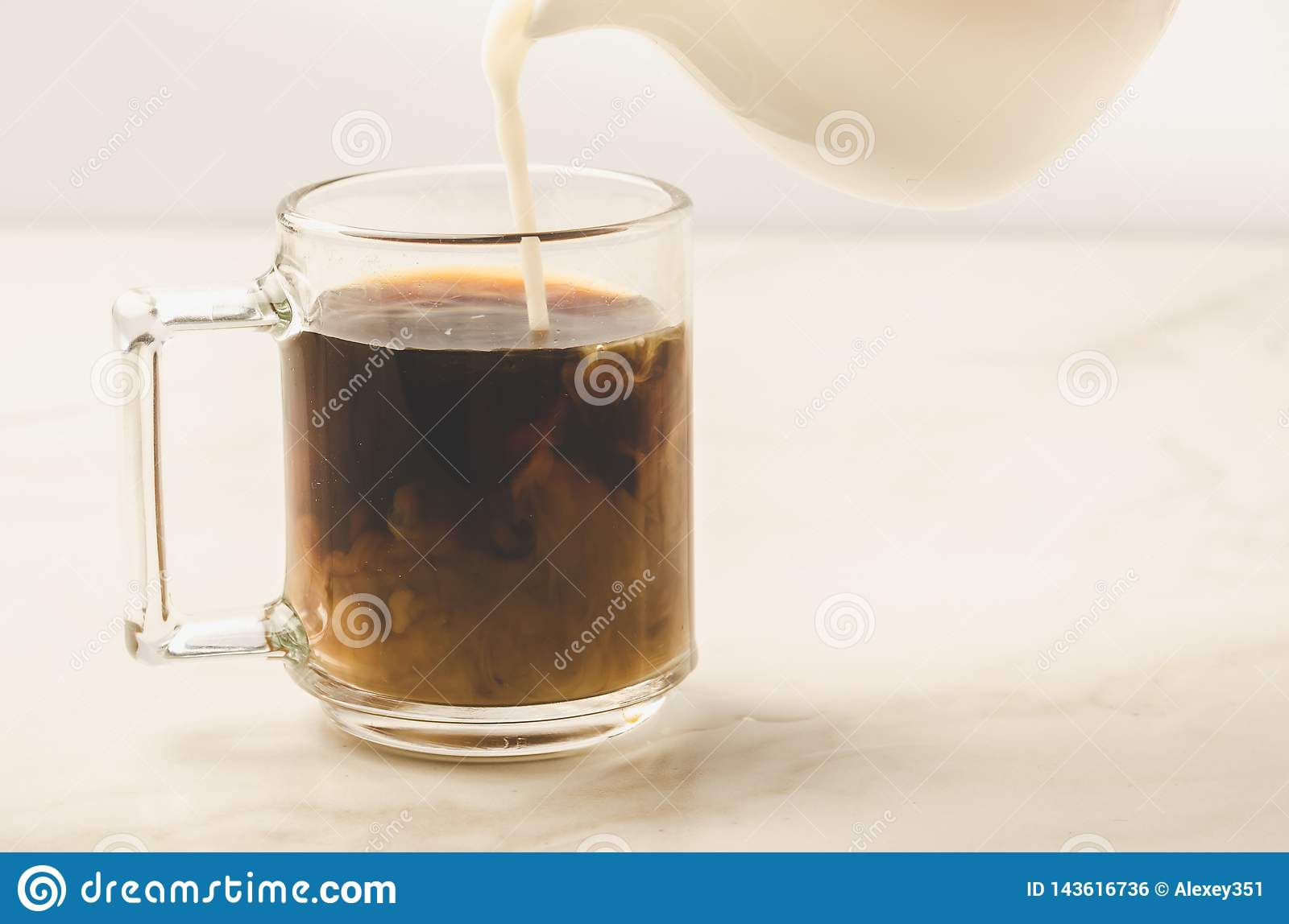 Milk is added to coffee glass/milk is added to coffee glass on white marble background. Selective focus