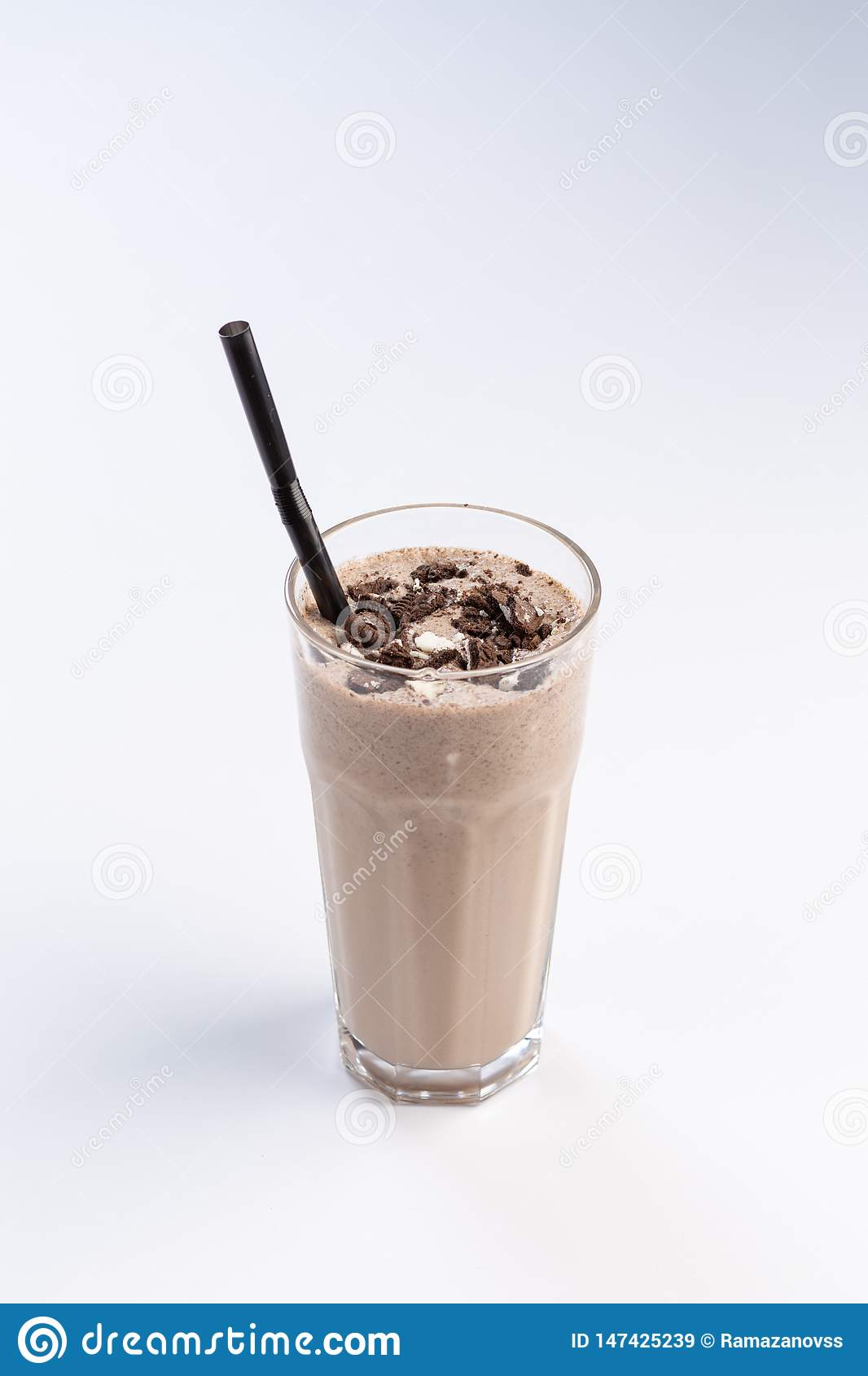 Milk-chocolate cocktail in a tall glass with a straw on white background
