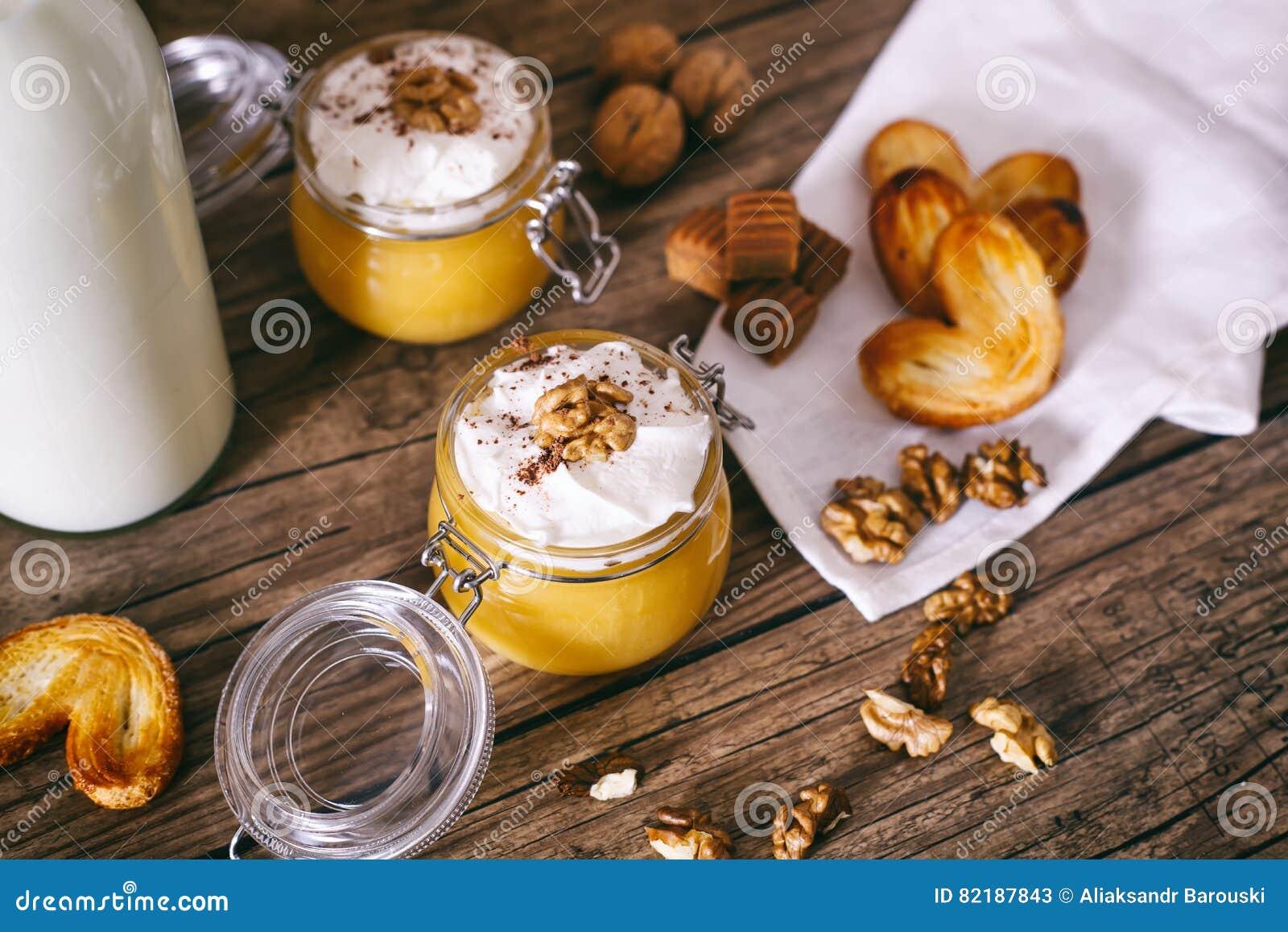 Milk shake da abóbora no frasco de vidro com as cookies do chantiliy, do caramelo, da noz e do mel Frasco do leite De madeira esc