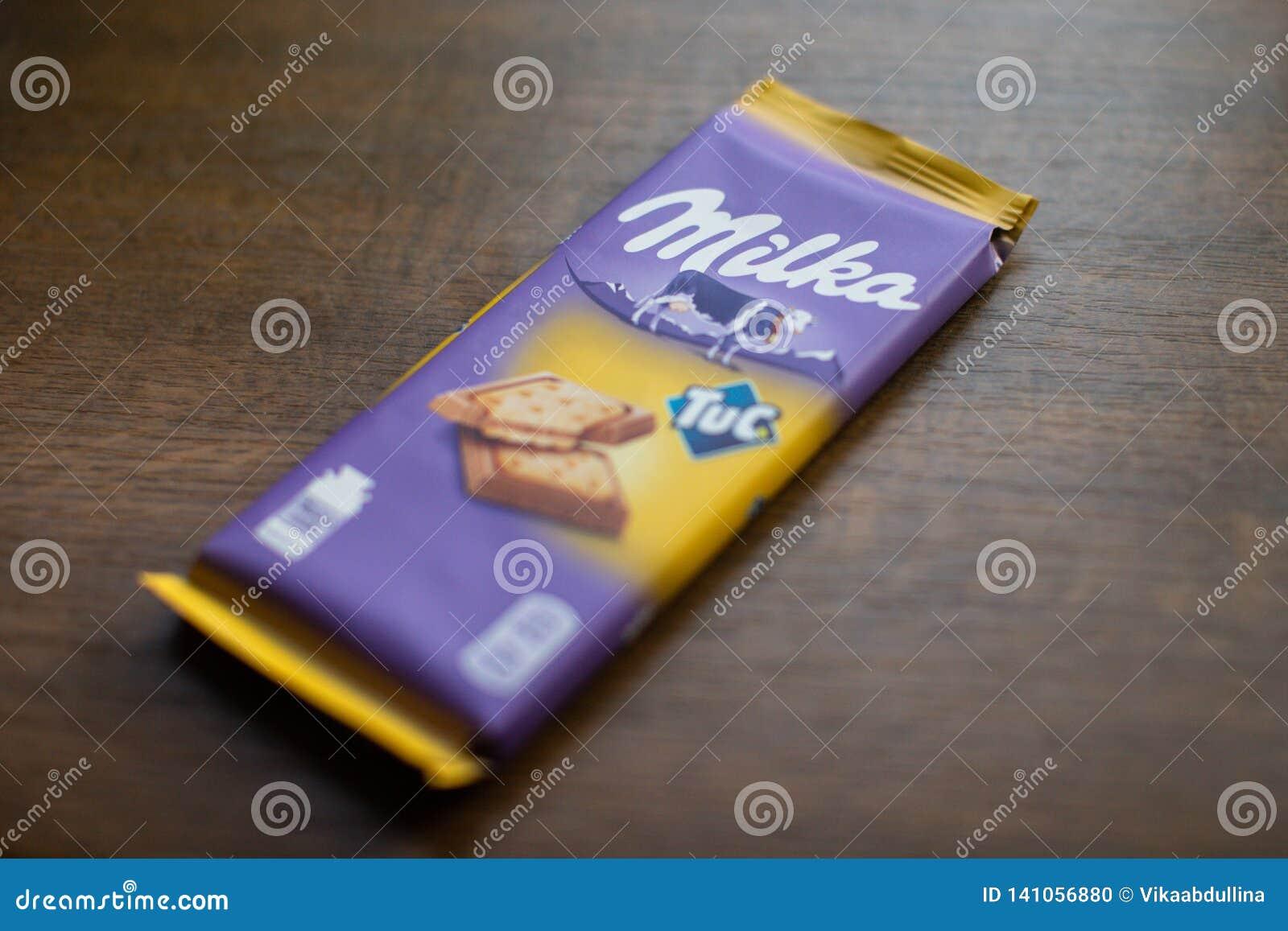 """Milkachocoladereep met Tuc-cracker met houten achtergrond Milka is een merk van chocoladegebak door Internationale MondelÄ """"z"""