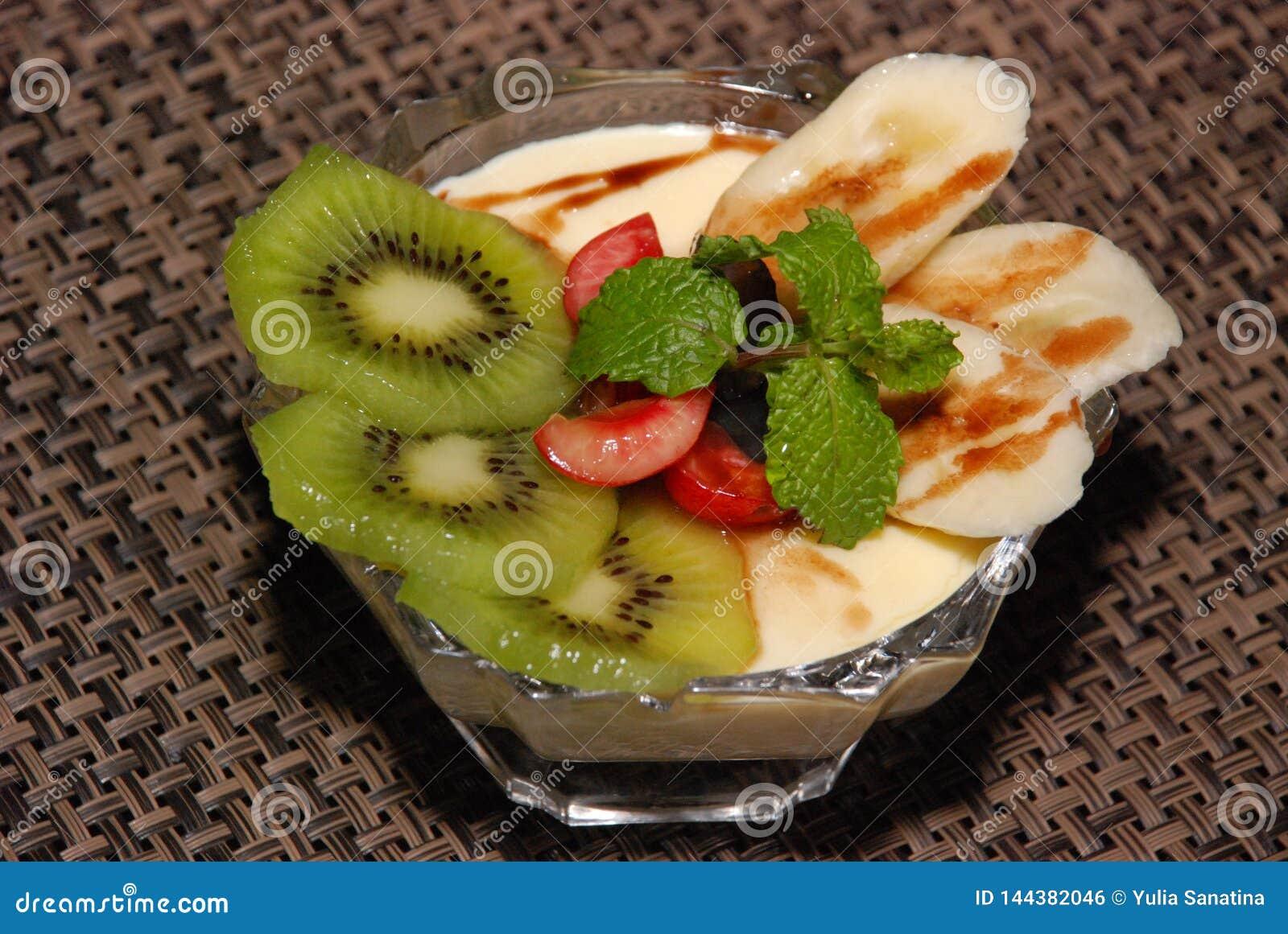 Milky desert with kiwi, cherry, banana, mint and chocolate toping