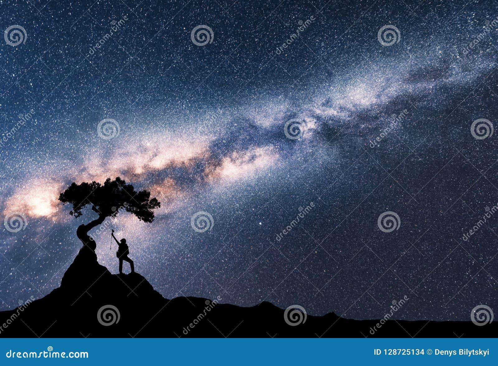 Milky sposób i sylwetka kobieta pod drzewem