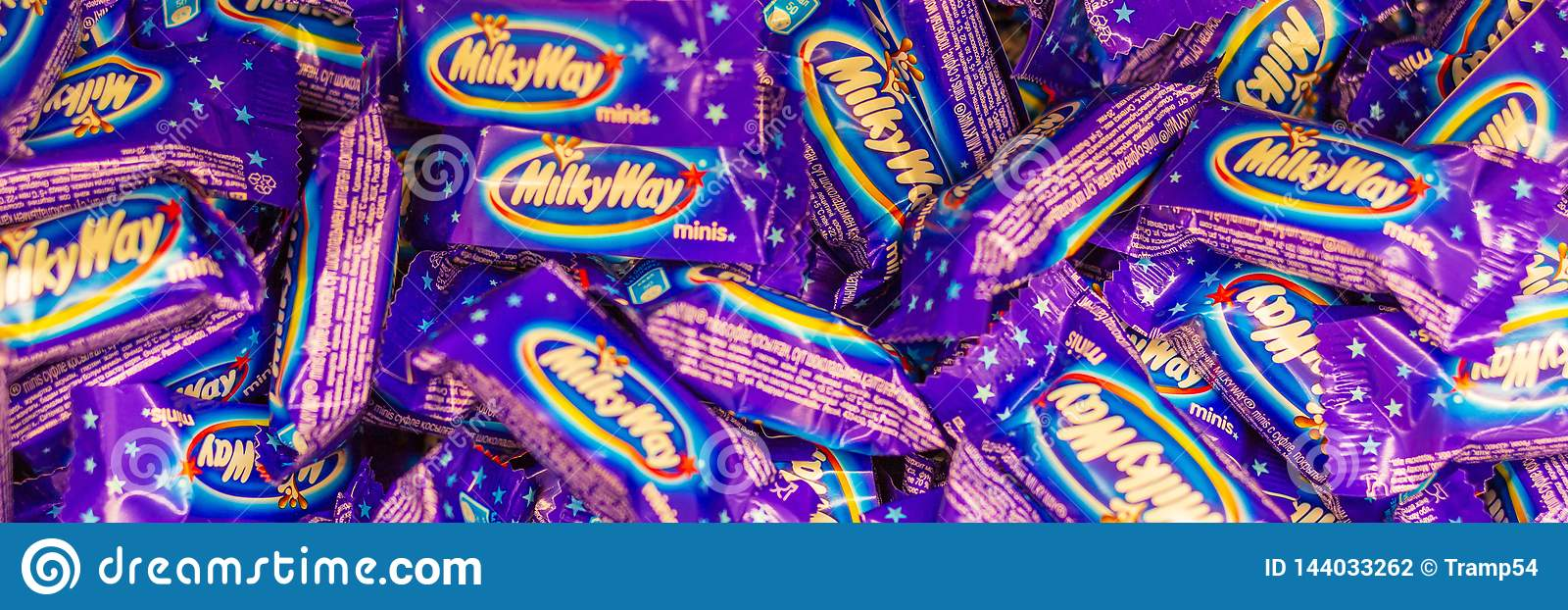 Milky Way chocolate bars on store shelves, texture. Text in Russian: chocolate bar