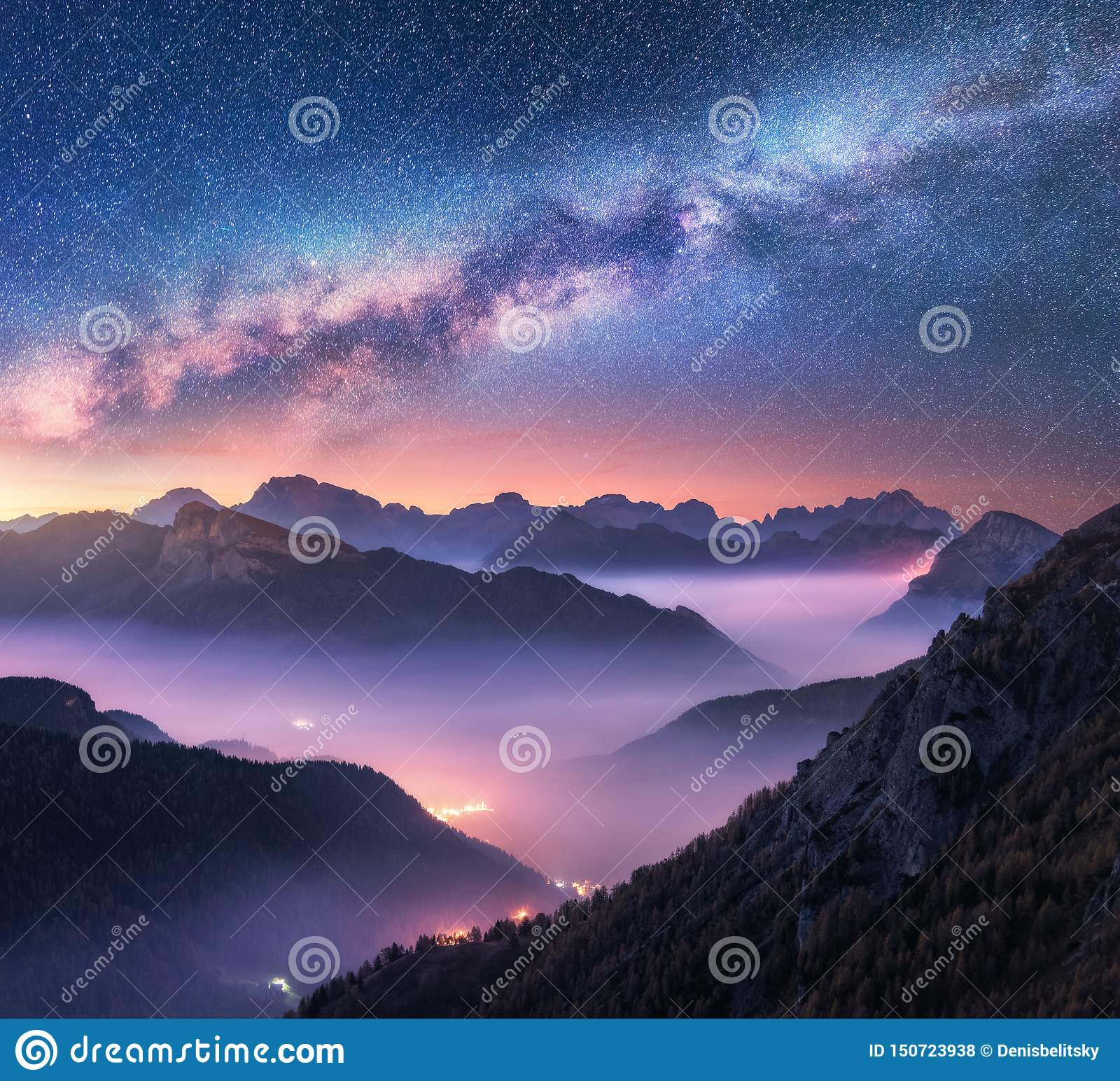 Milky Way over mountains in fog at night in summer. Landscape