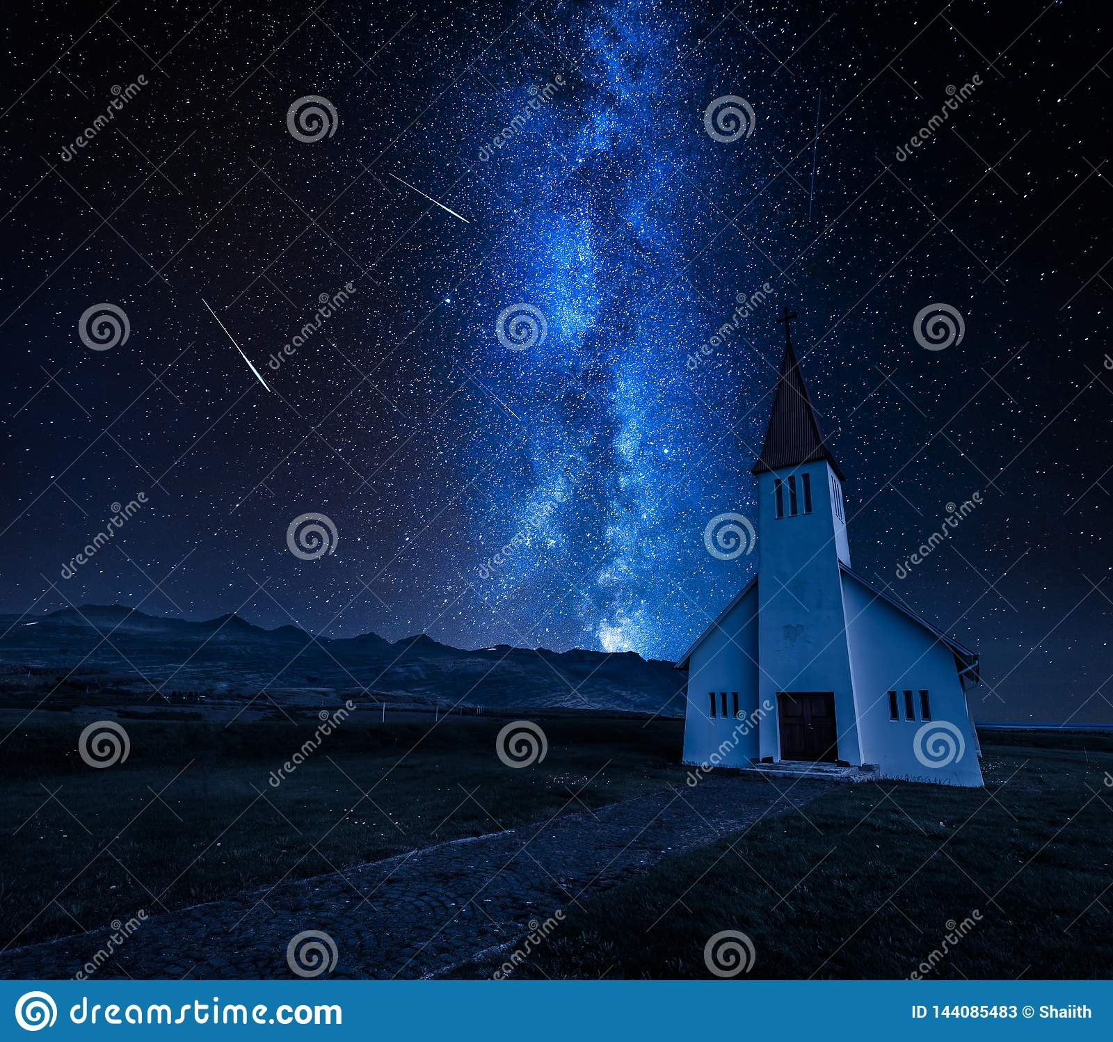 Milky way over small church in mountain, Iceland in summer
