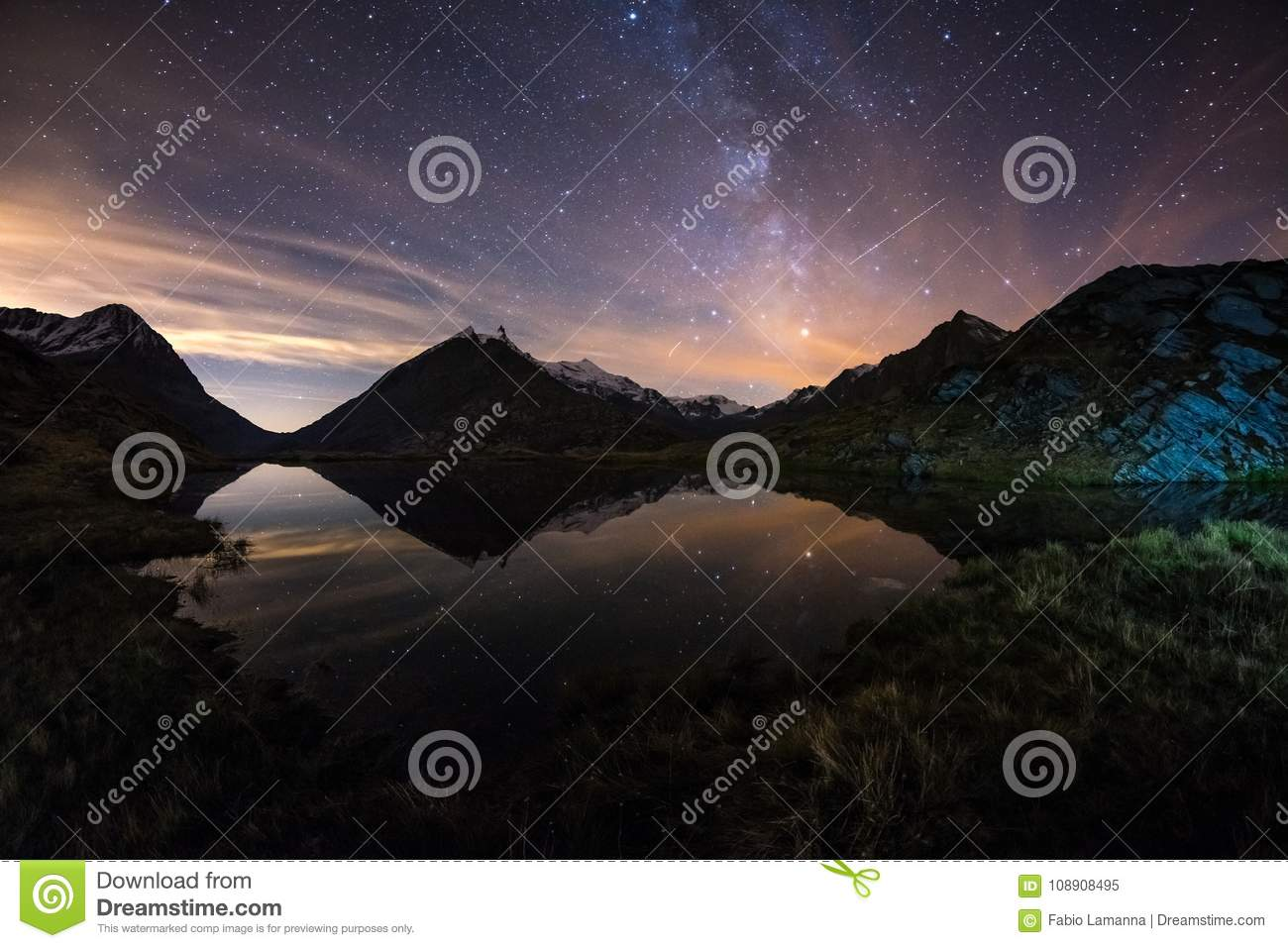 Milky Way starry sky reflected on lake at high altitude on the Alps. Fisheye scenic distortion and 180 degree view.