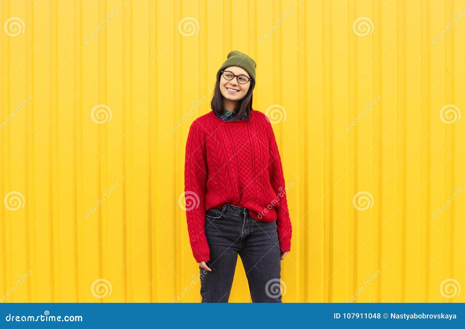 Millenialmeisje im modieuze kleren die een goede tijd hebben, die grappige gezichten maken dichtbij heldere gele stedelijke muur