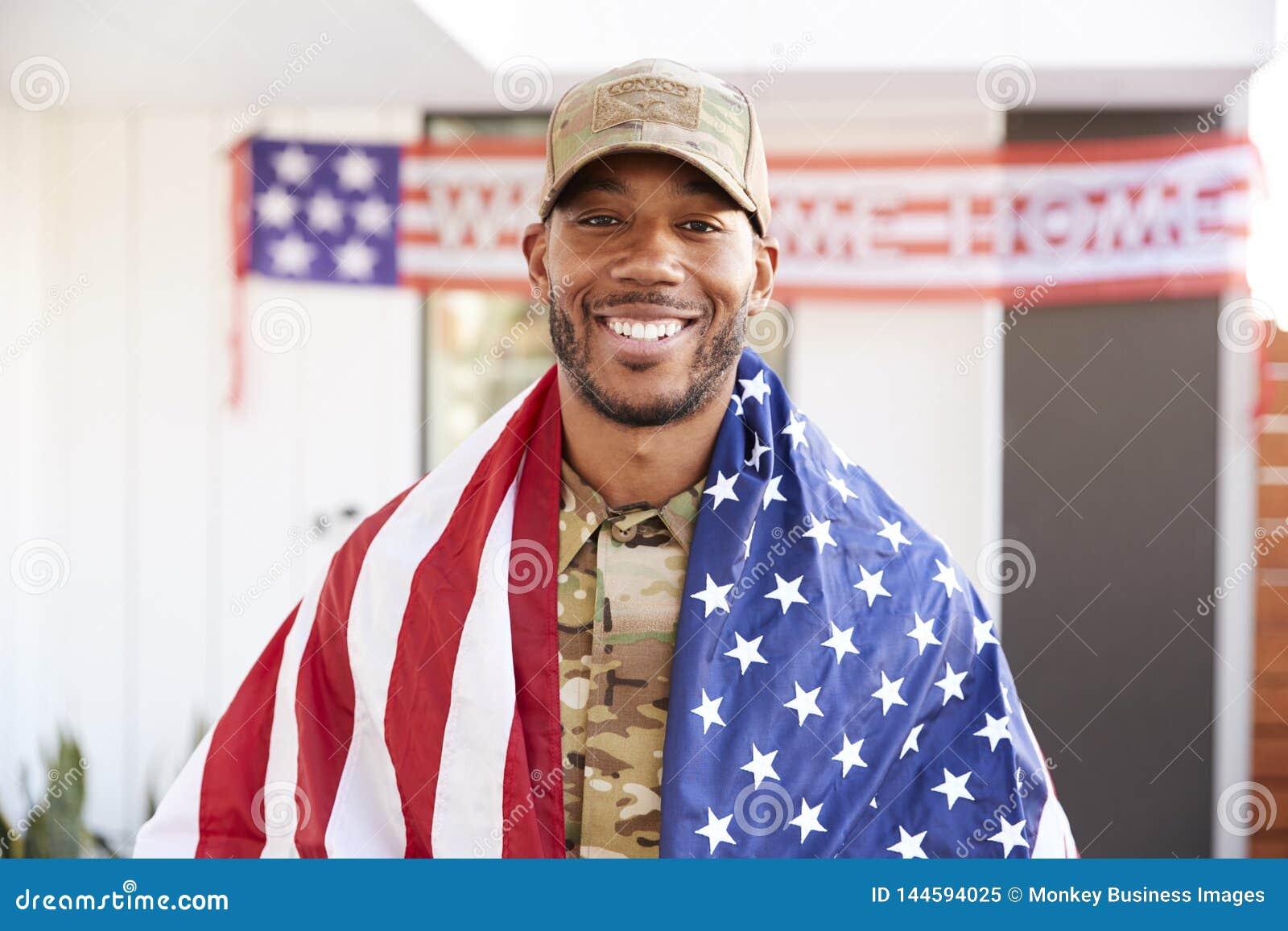 Millennial afrikansk amerikansoldat med USA-flaggan som draperas över hans skuldror som ler till kameran, slut upp