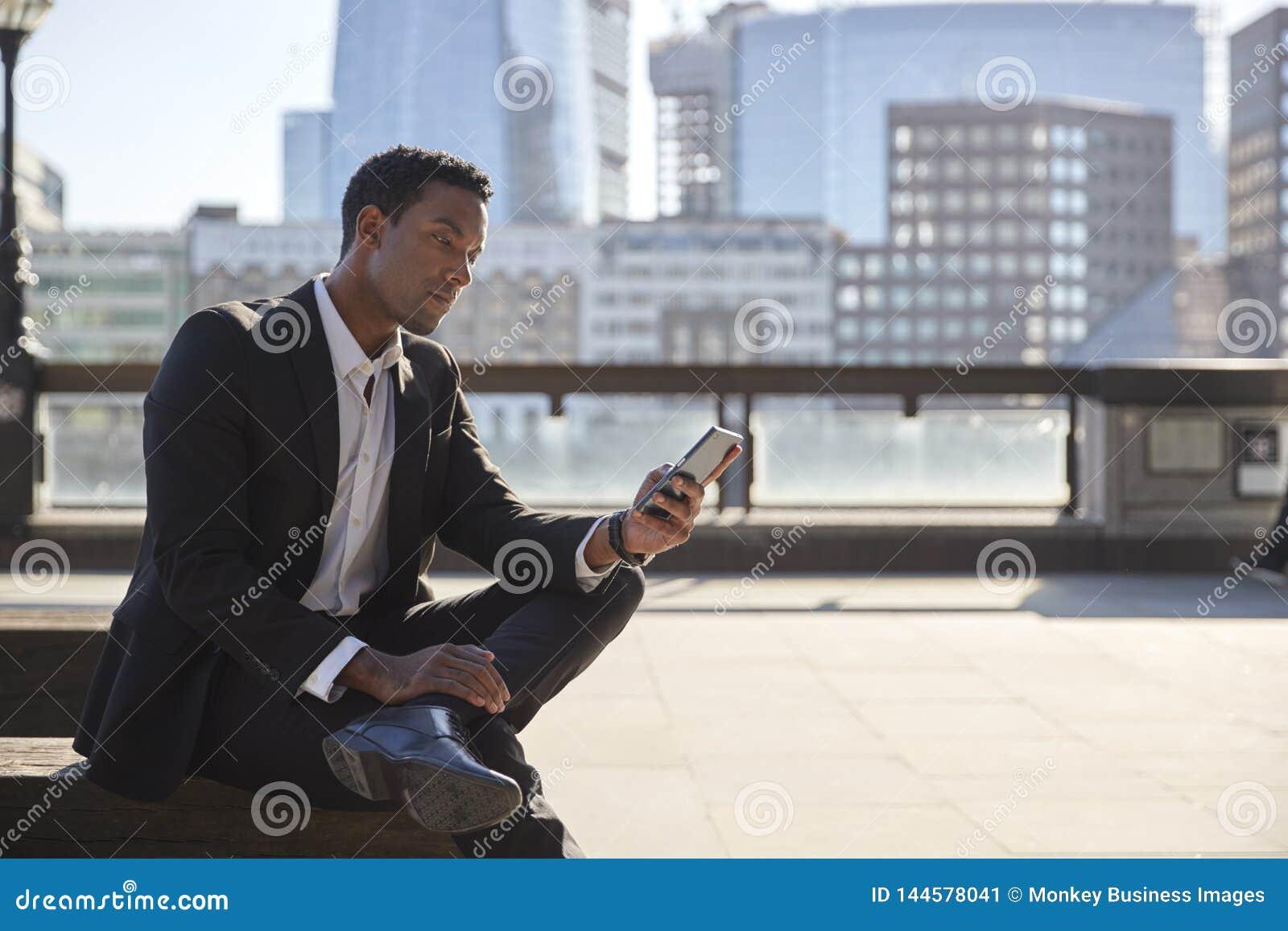 Millennial biznesmen jest ubranym czarnego kostium i białego koszulowego obsiadanie na Rzecznym Thames bulwarze używać smartphone