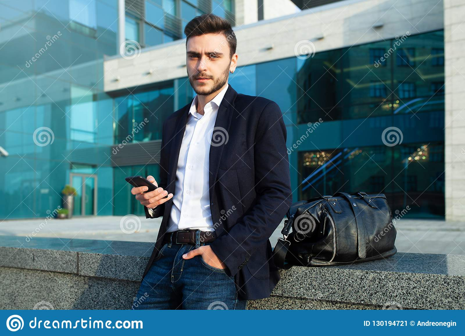 Millennial businessman with a mobile phone in his hands. Young successful business stylish man with a black leather bag
