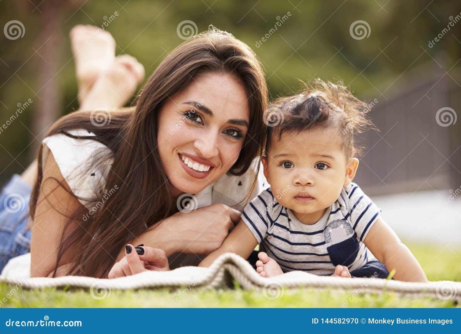 Millennial latynos matki lying on the beach na koc w parku z jej dzieckiem, ono uśmiecha się kamera, zakończenie w górę
