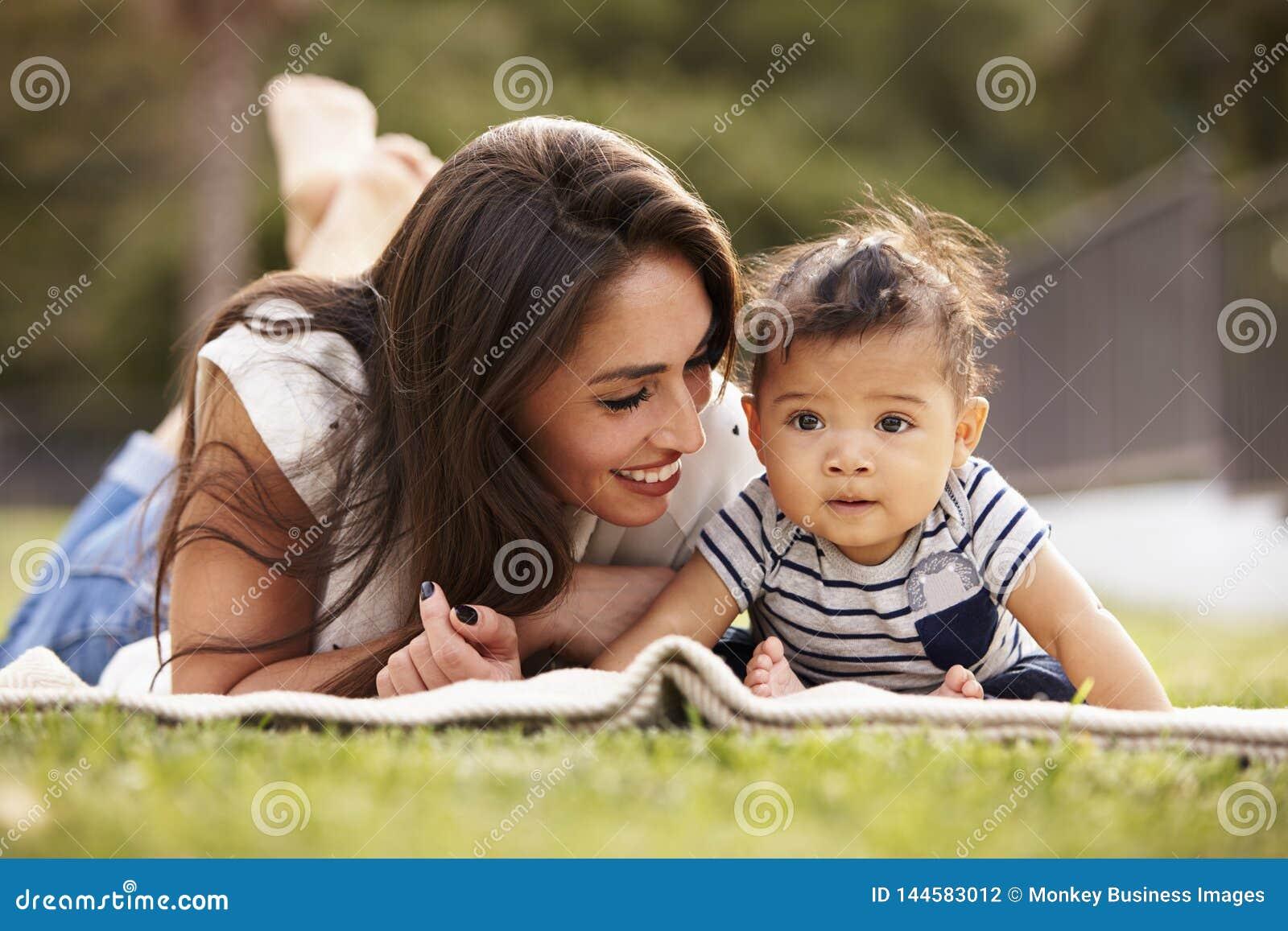 Millennial latynos matki lying on the beach na koc w parku z jej dzieckiem ono uśmiecha się, zakończenie w górę