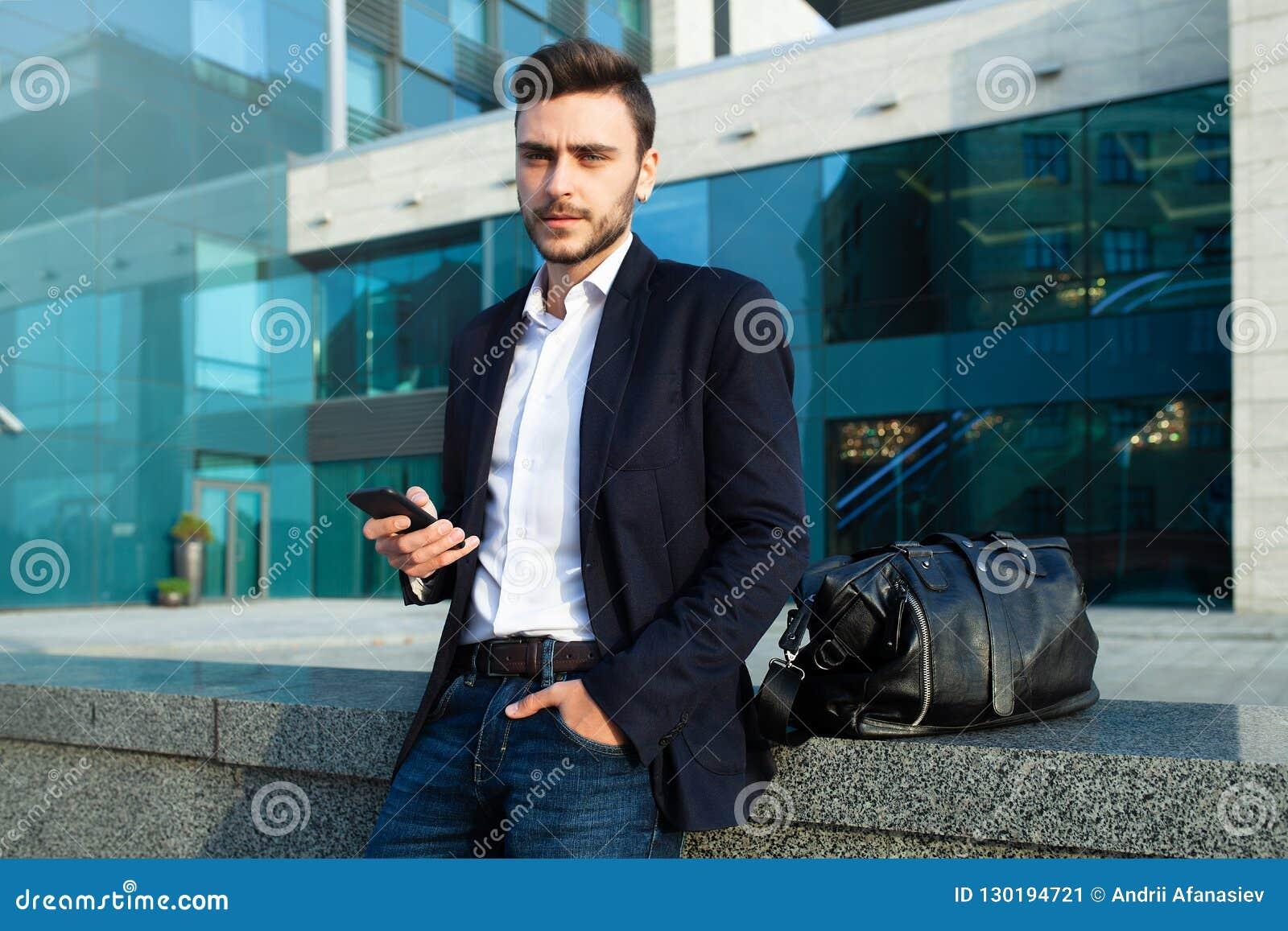 Millennial zakenman met een mobiele telefoon in zijn handen Jonge succesvolle bedrijfs modieuze mens met een zwarte leerzak