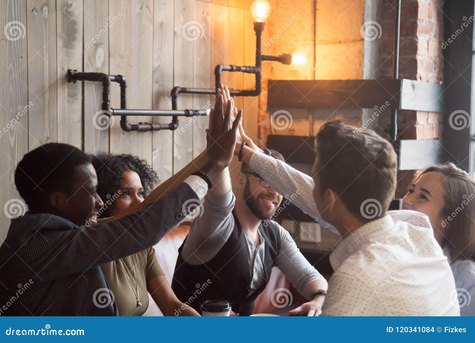 Millennials de sourire donnant la haute cinq au cours de la réunion en café