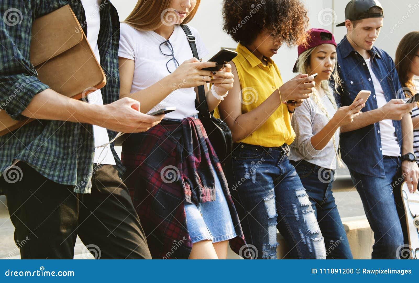 Millennials unter Verwendung der Smartphones der Verschiedenartigkeit draußen