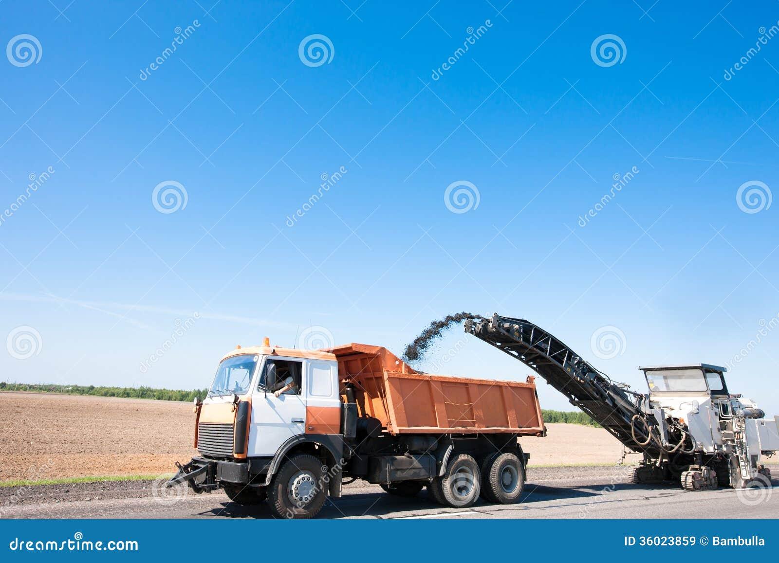 Milling machine removing crushed aphalt into dump truck