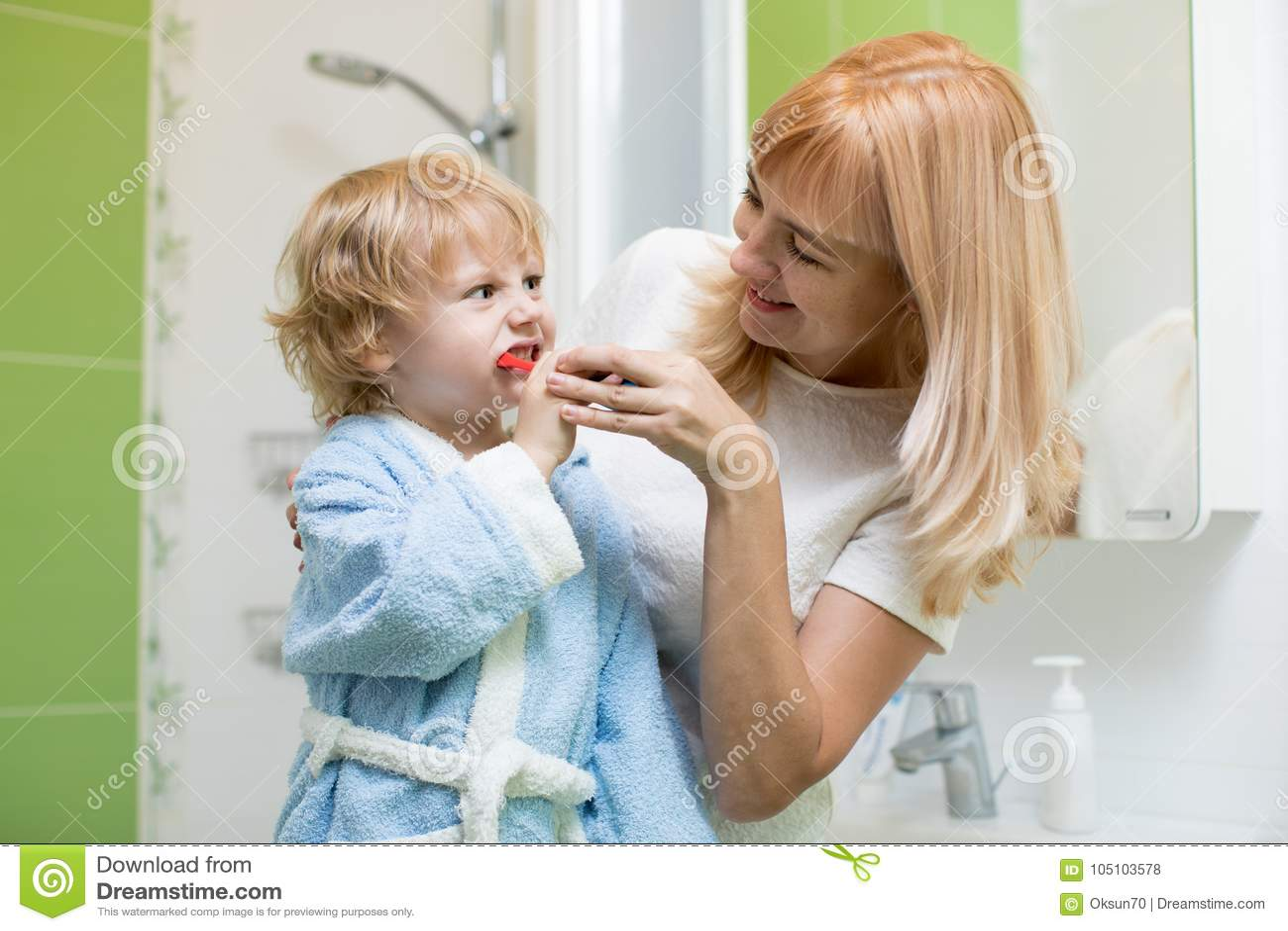 Mime al hijo de enseñanza y de ayuda del niño cómo cepillar sus dientes