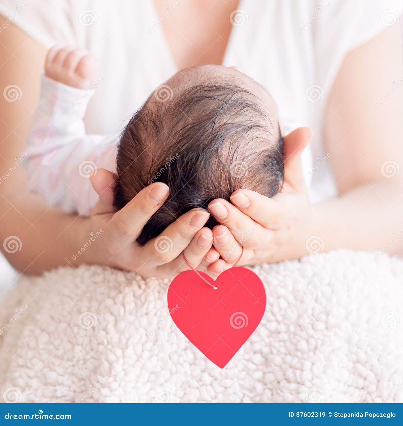 Mime a llevar a cabo la cabeza de su bebé recién nacido en manos Familia feliz c
