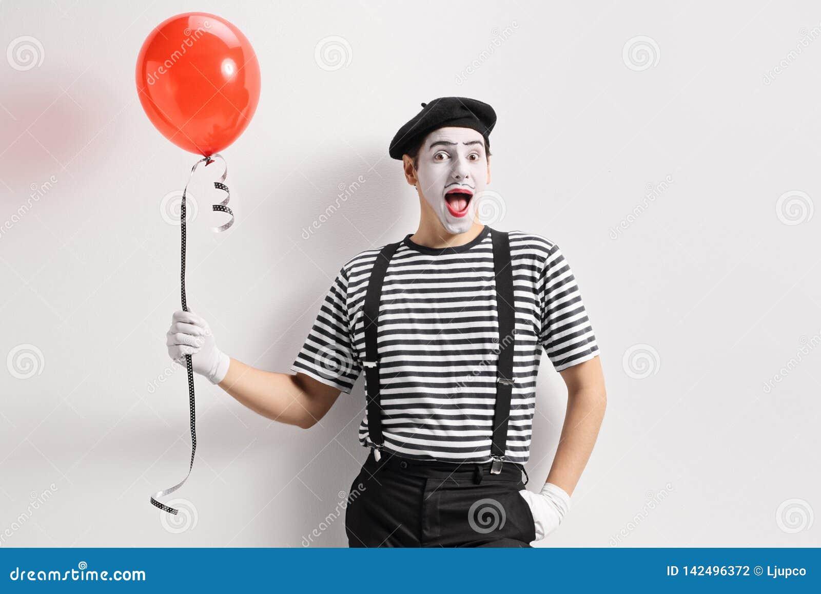 Mime que sostiene un globo rojo y que se inclina contra la pared