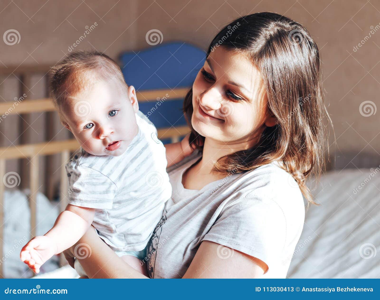 Mime a sentarse con el bebé en cama y a jugar el abrazo