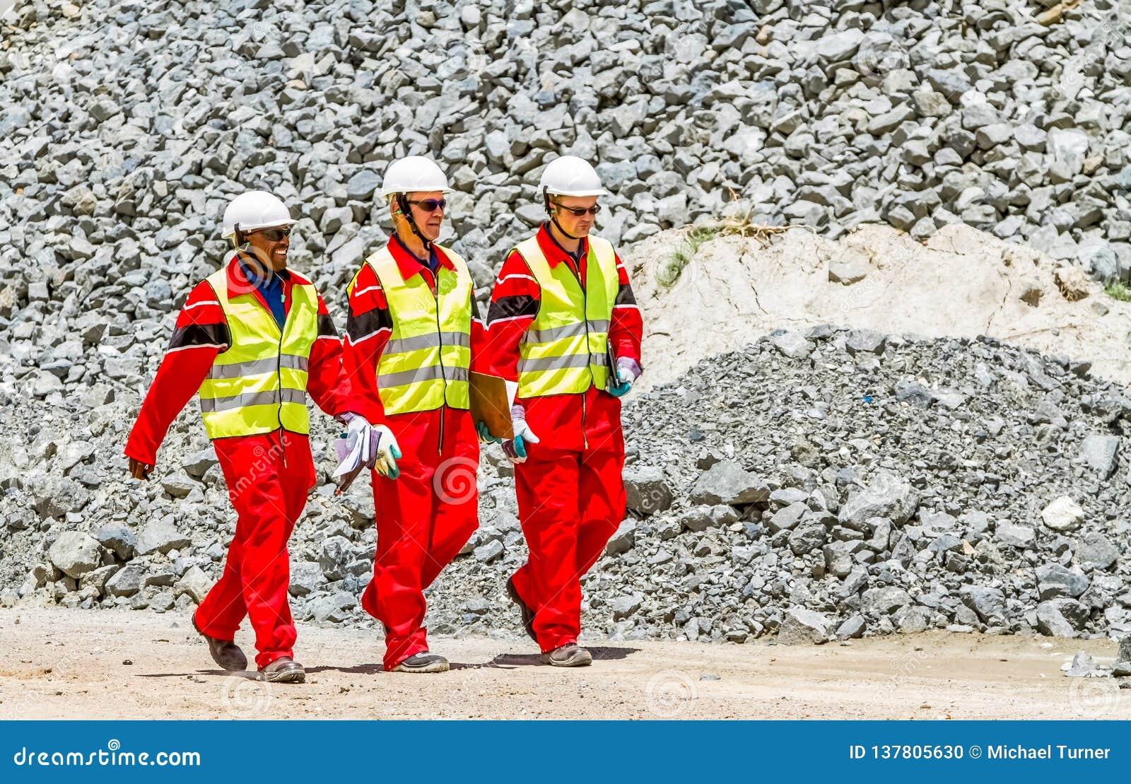 Minério da platina do transporte de correia transportadora para processar com os inspetores da segurança de mineração que verific