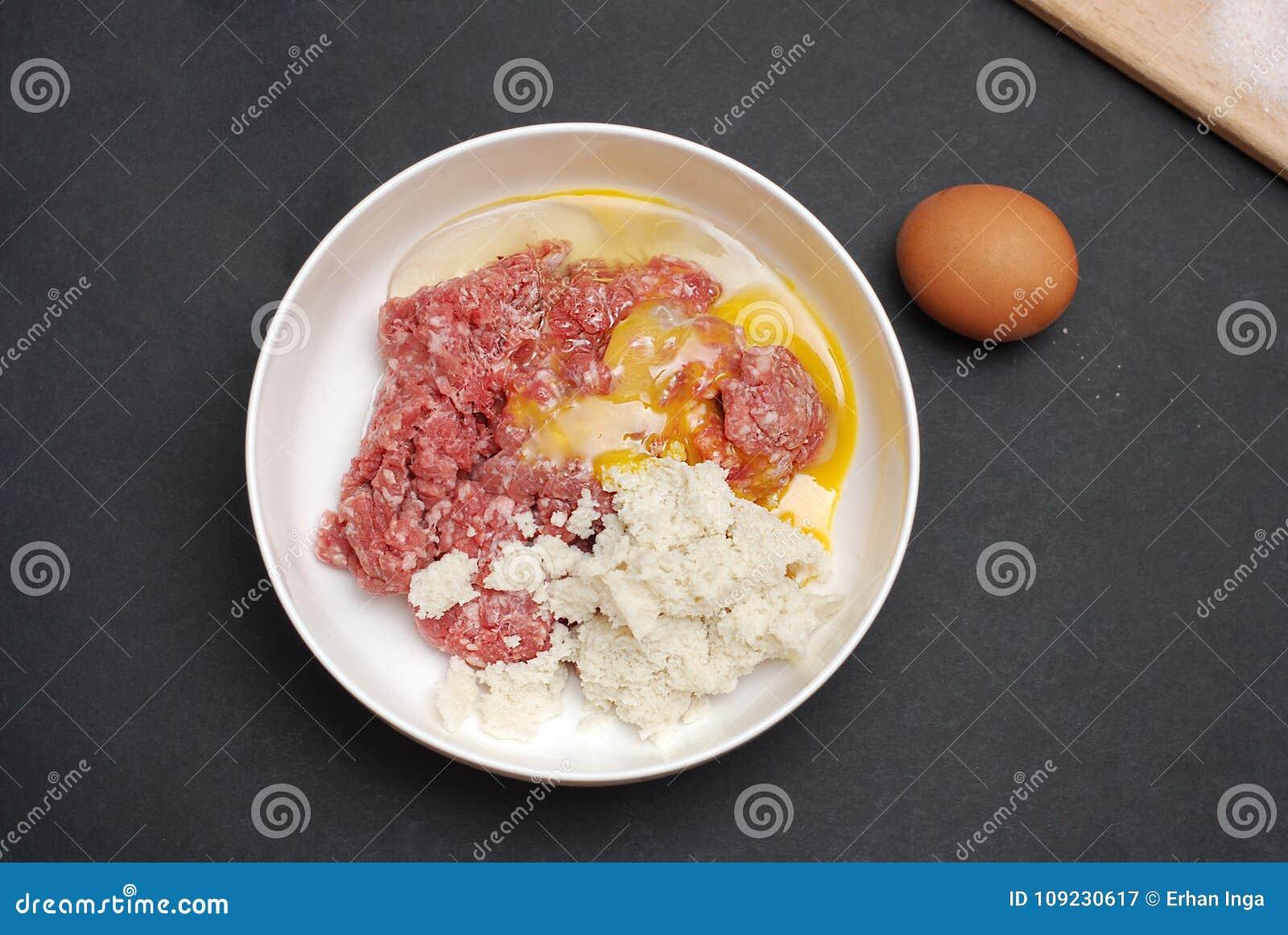 Minced mięso w pucharze z pikantność i jajkiem na Ciemnym tle Odgórny widok, czarny tło