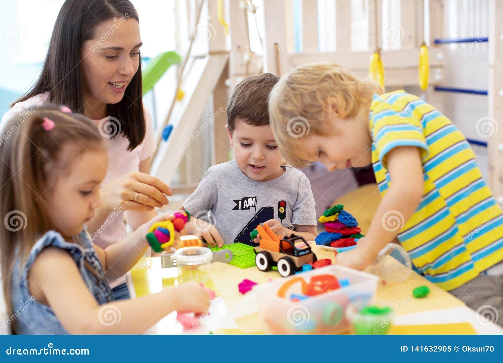 Minder do bebê que joga com as crianças no centro de centro de dia