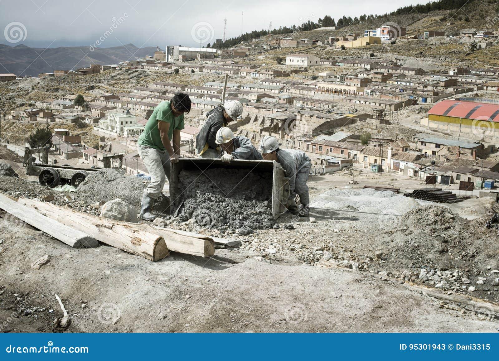 Mineros que vacian el carro de la mina en la mina de plata de Cerro Rico en Potosi
