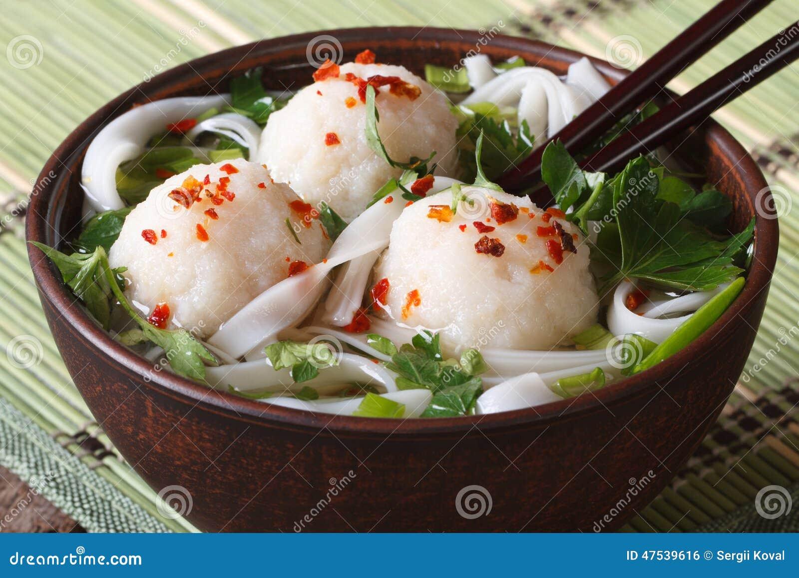 Minestra asiatica con le palle di pesce, le erbe fresche e la fine-u delle tagliatelle di riso