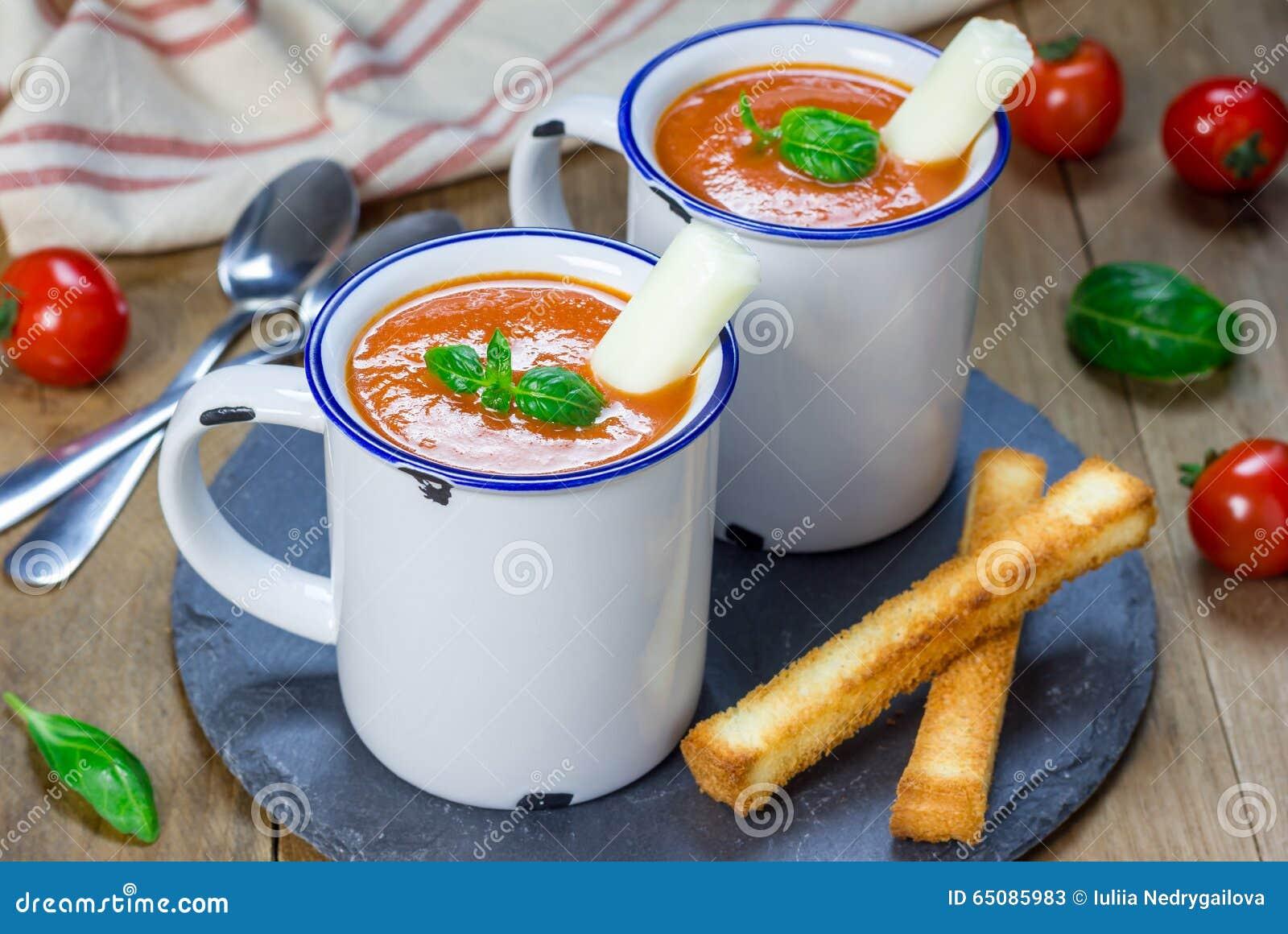 Minestra casalinga del basilico del pomodoro nella tazza, servita con il bastone del formaggio della mozzarella
