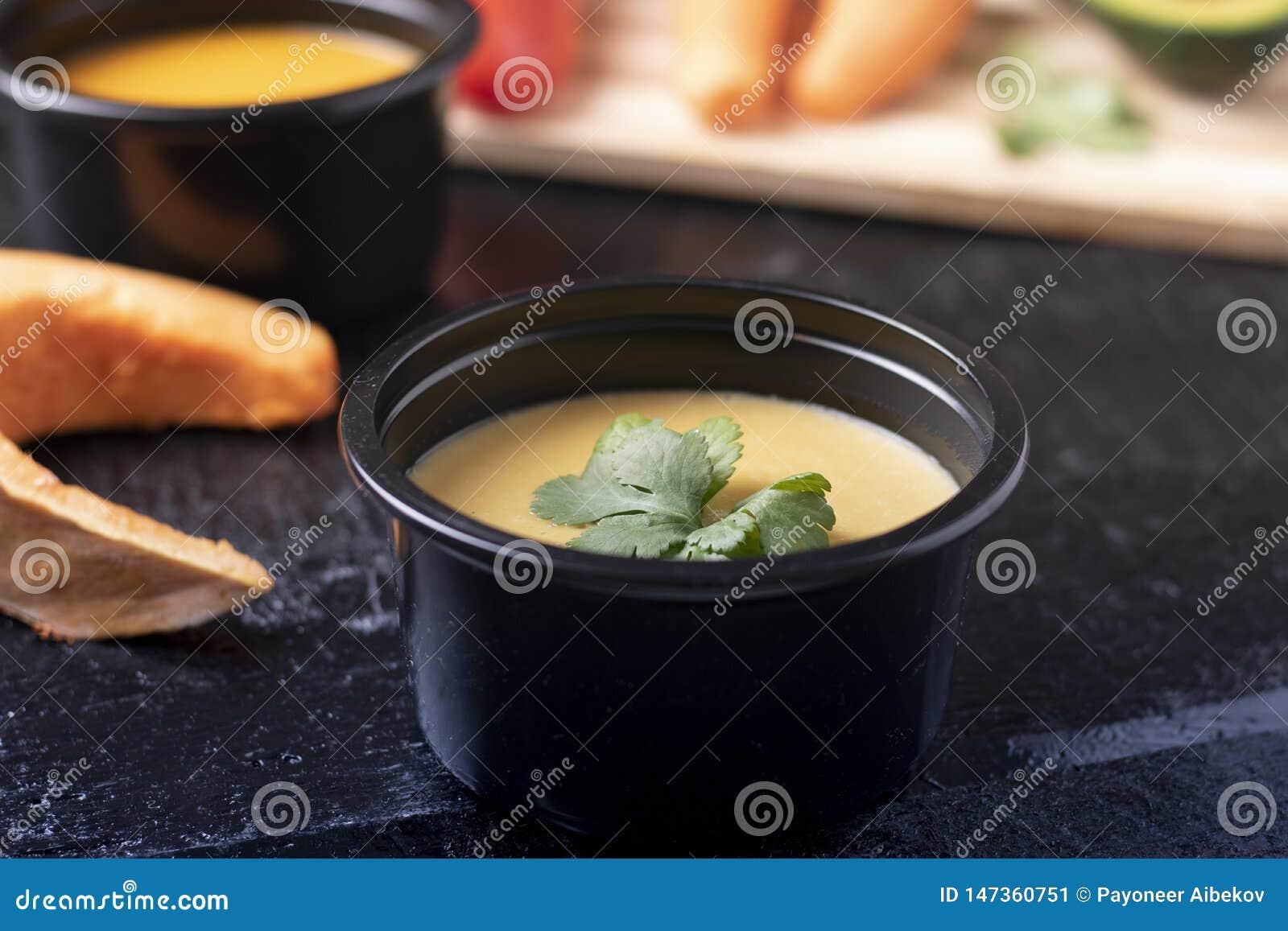 Minestra della zucca e porridge delle foglie di menta, del cucchiaio, del pepe e del pisello in contenitore di alimento sulla tav