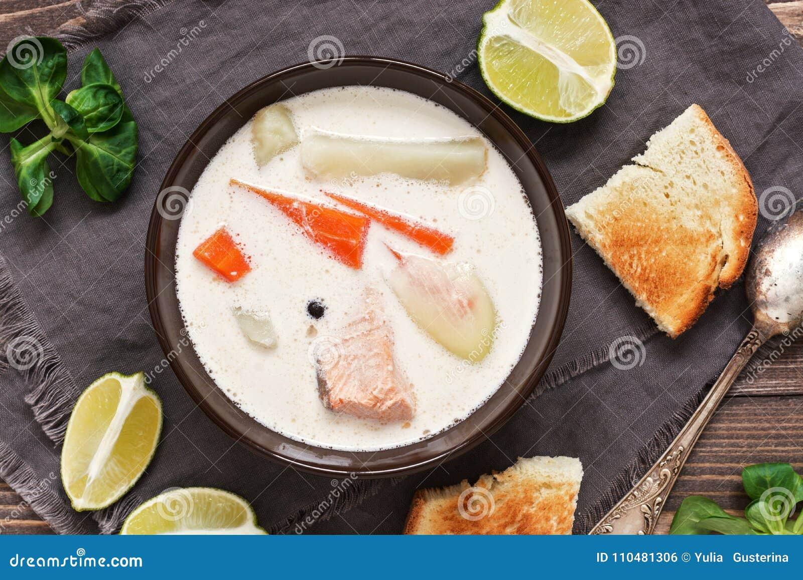 Minestra di color salmone con le patate, carote, crema Minestra scandinava e norvegese del pesce su un fondo di legno rustico pri