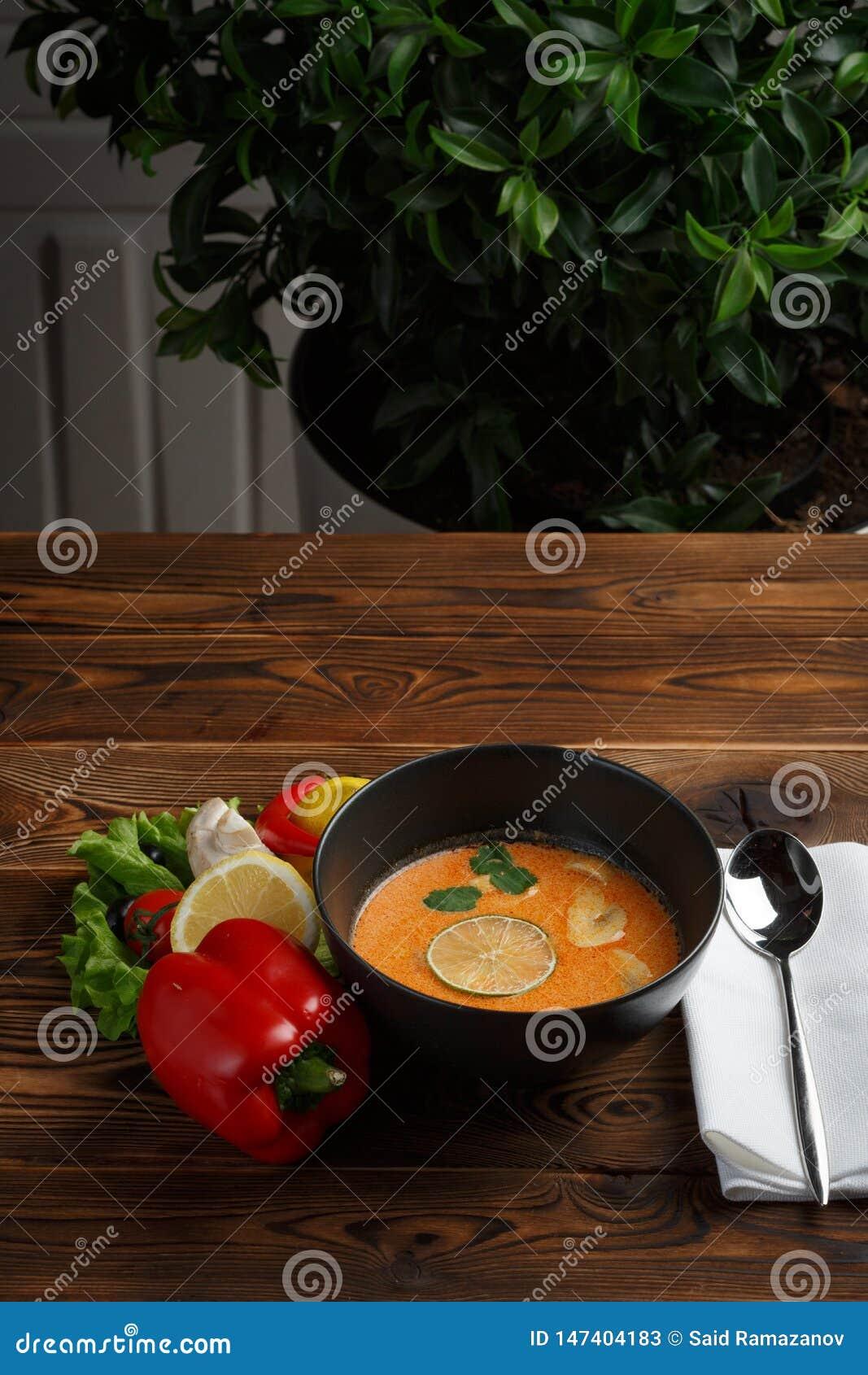 Minestra di kha di Tom con il limone e le verdure su un fondo di legno