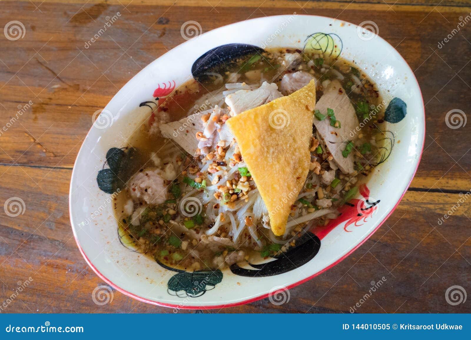 """Minestra tailandese """"di Tom Yum """"della tagliatella con carne di maiale e lo gnocco croccante"""