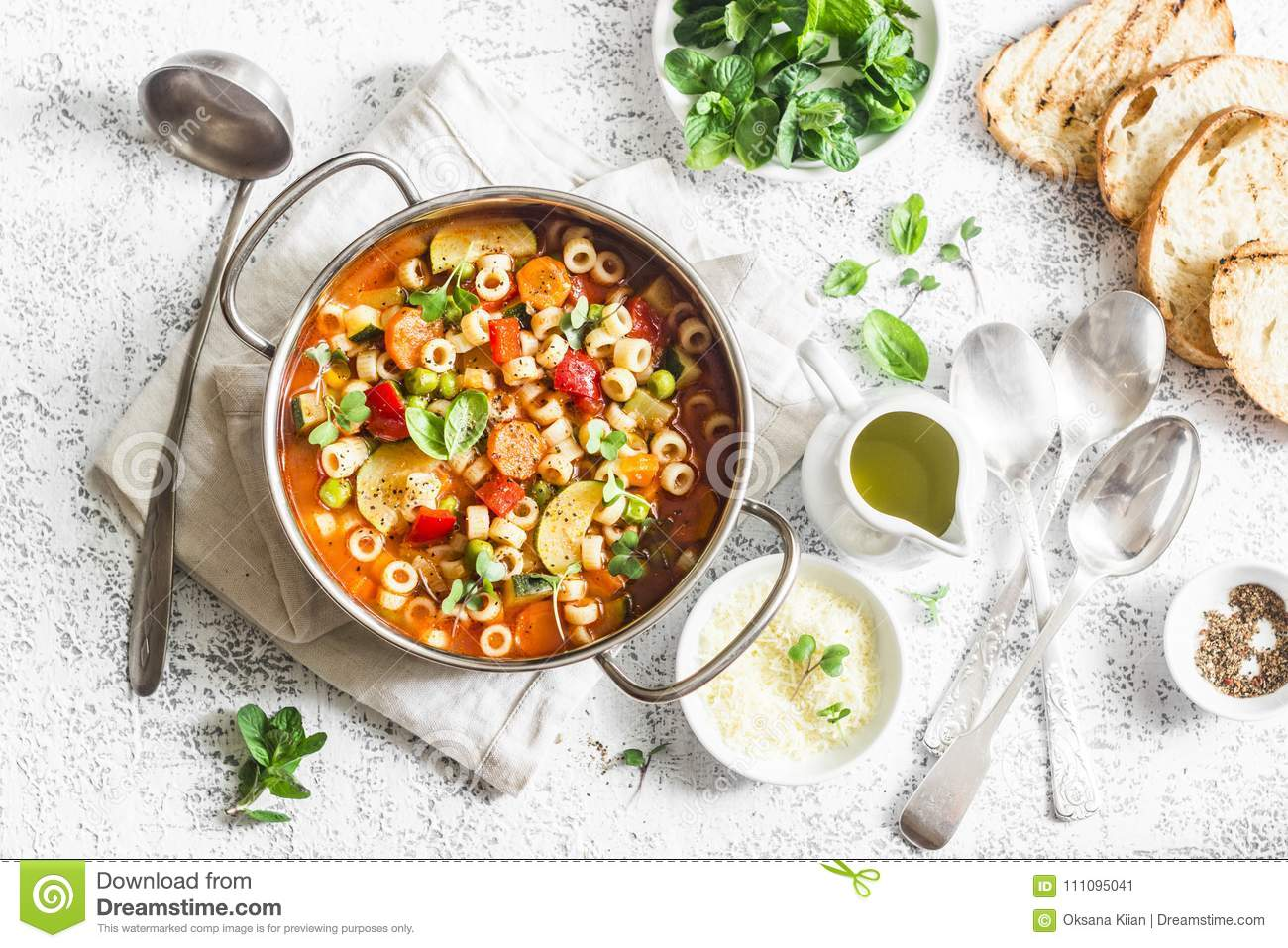 Minestrone soup in a pan on a light table, top view. Italian soup with pasta and seasonal vegetables. Delicious vegetarian food co