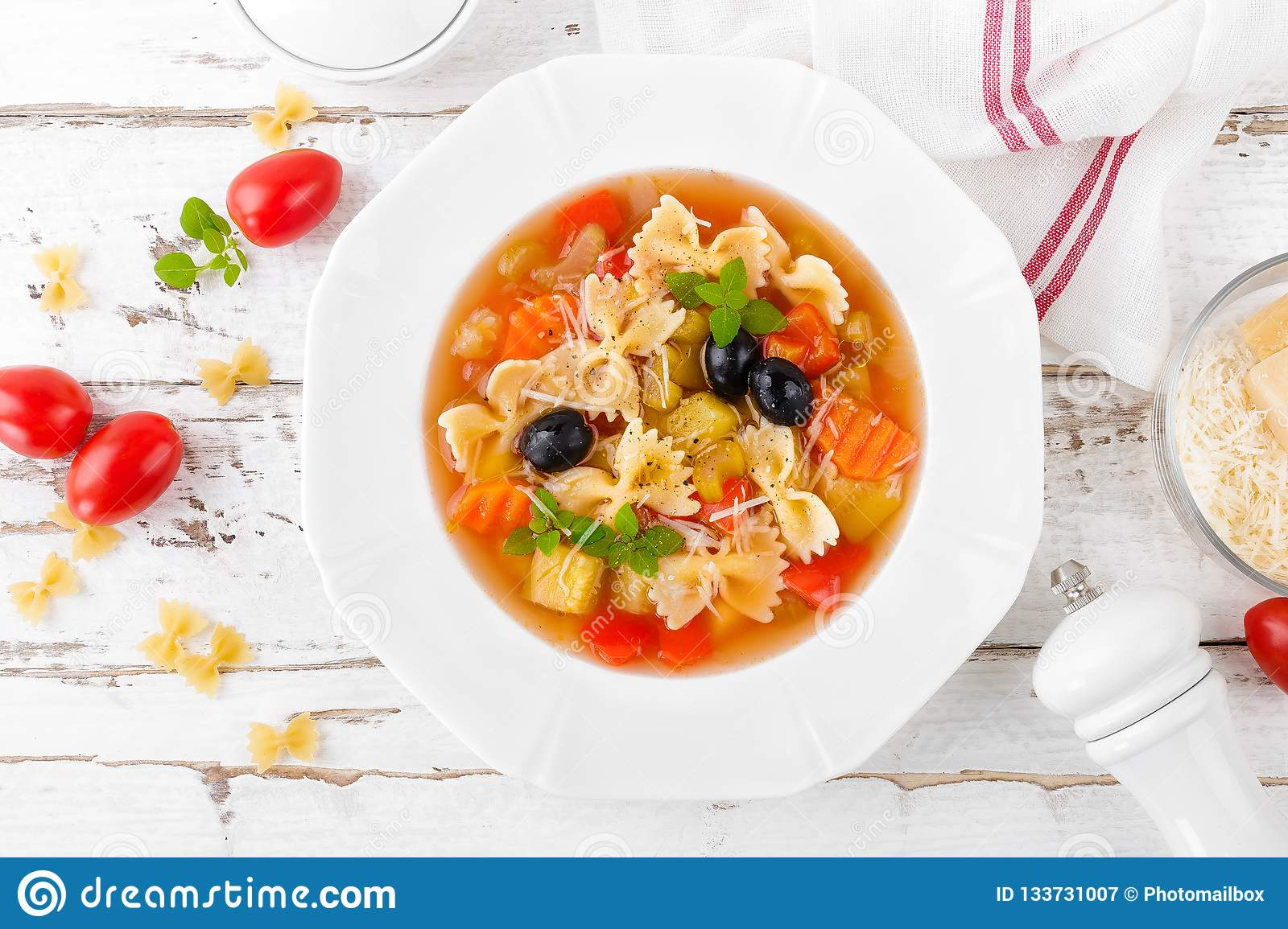 Minestrone, vegetarian soup with pasta and vegetables on white wooden rustic background. Traditional italian food