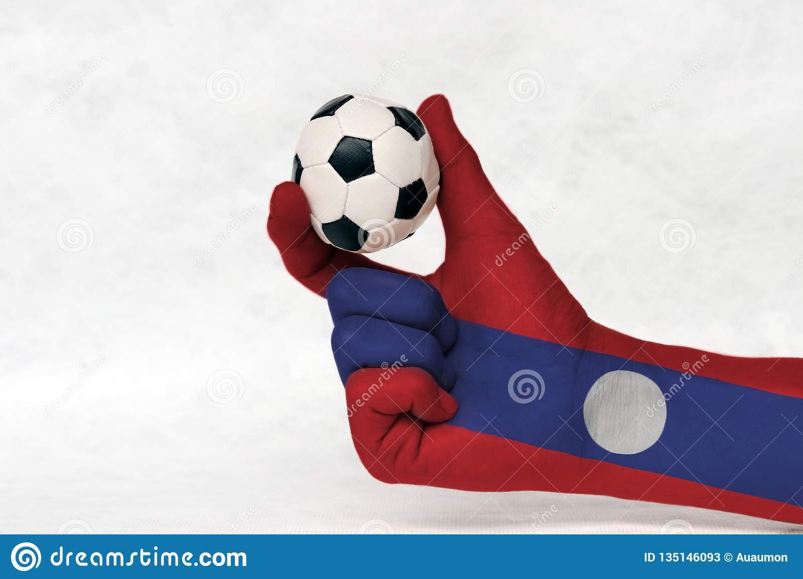 Mini ball of football in Laos flag painted hand, hold it with two finger on white background.