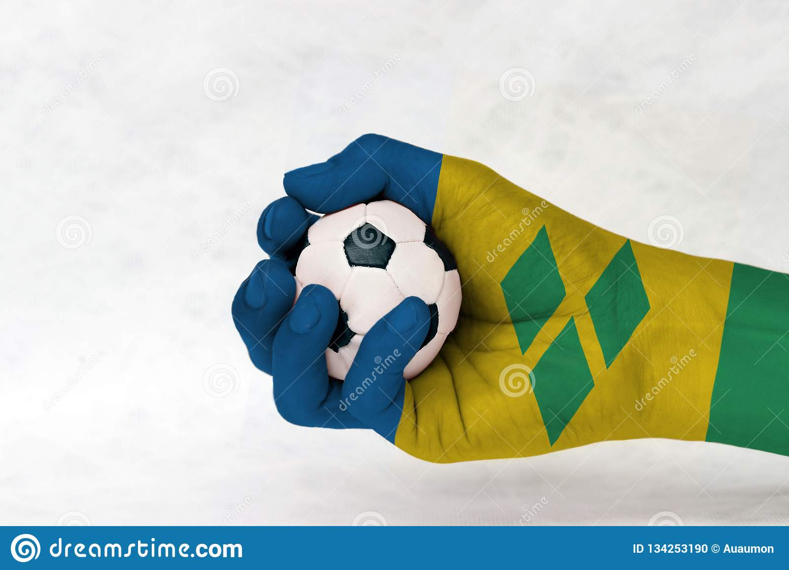 Mini ball of football in Saint Vincent flag painted hand on white background. Concept of sport or the game in handle or minor matt