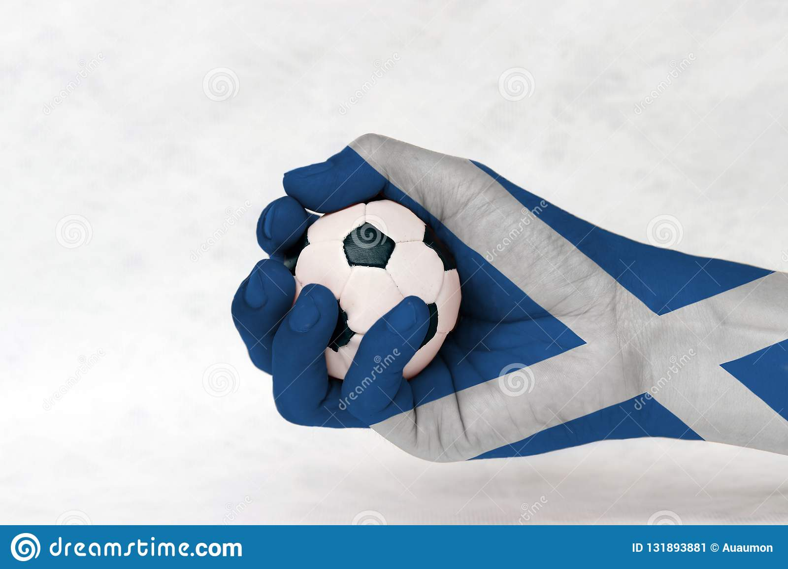 Mini ball of football in Scotland flag painted hand on white background. Concept of sport or the game in handle or minor matter.