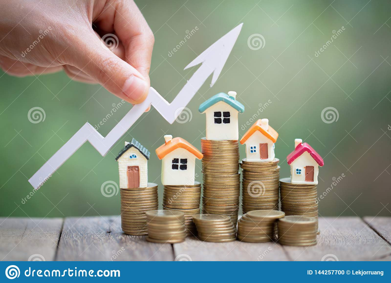 Mini casa modelo na pilha das moedas, no negócio crescente, no investimento da propriedade e no conceito financeiro da hipoteca d