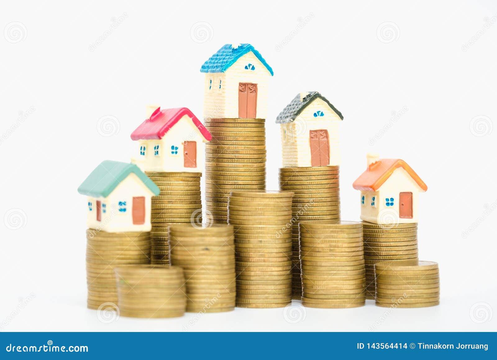 Mini casa na pilha de moedas, isolada no fundo branco, conceito da propriedade do investimento